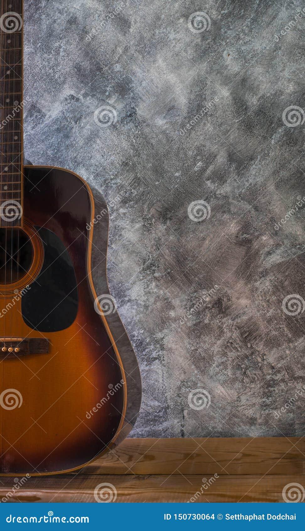 Akoestische gitaar die tegen op houten lijst een lege cementmuur rusten