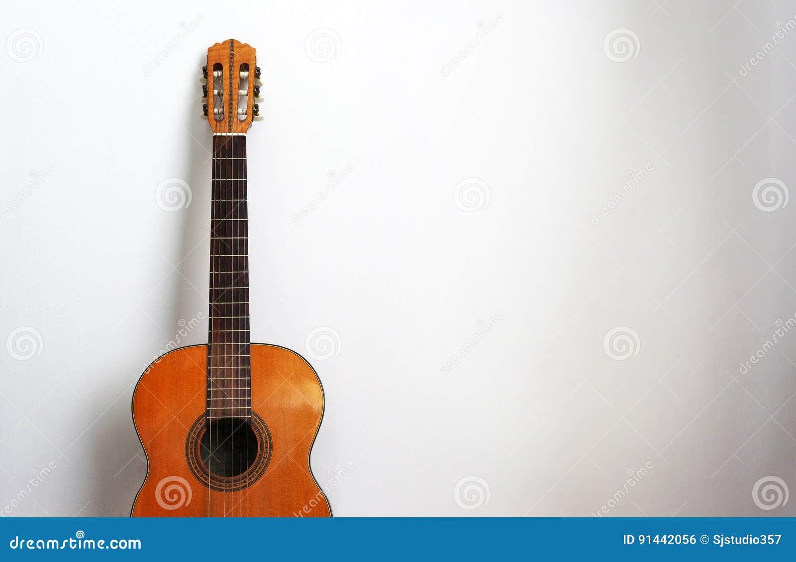 Akoestische gitaar op een witte muurachtergrond