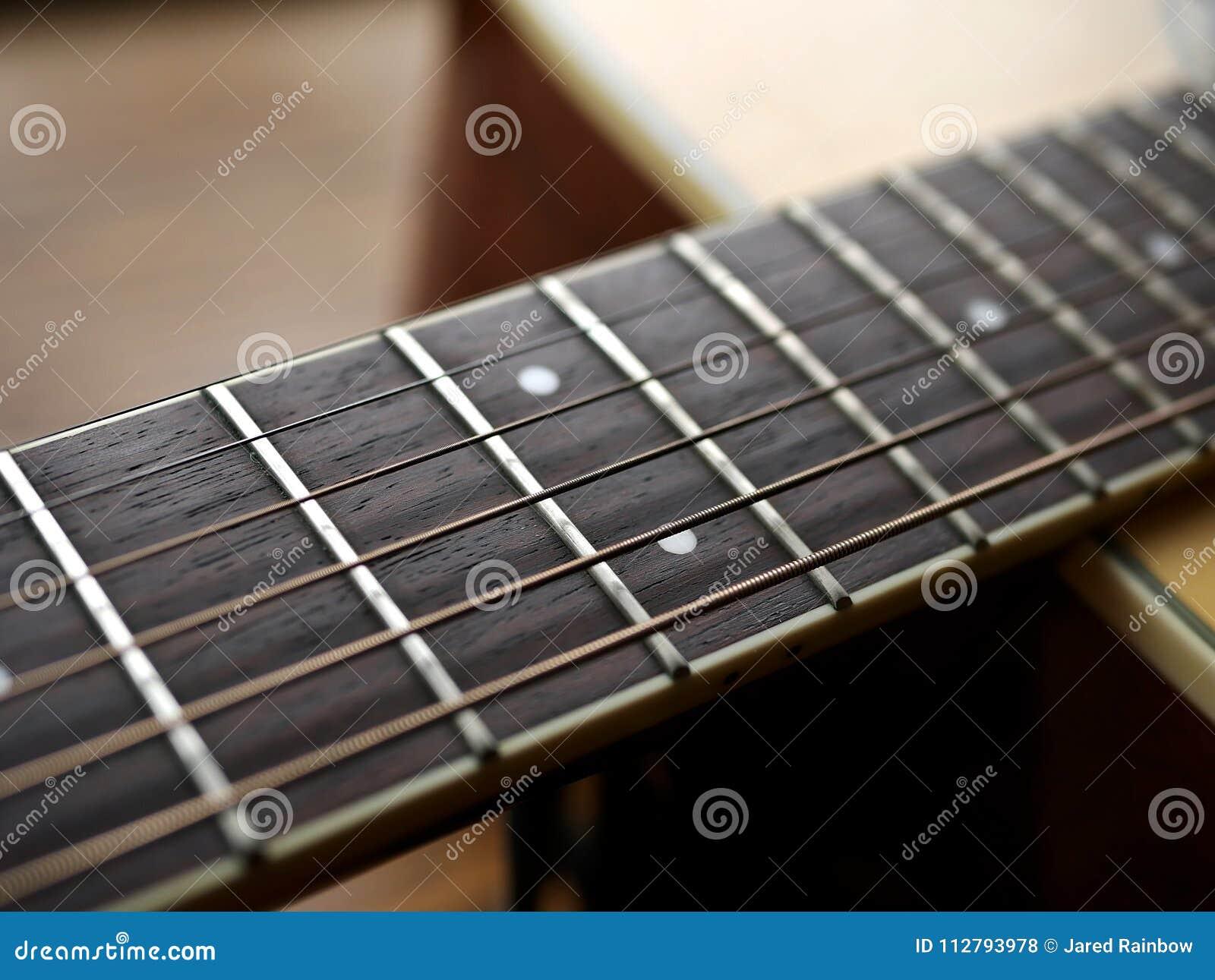 Akoestische houten gitaar dichte omhooggaand op houten achtergrond met fretboard, koorden, en tuners voor muziekbloggen, websiteb