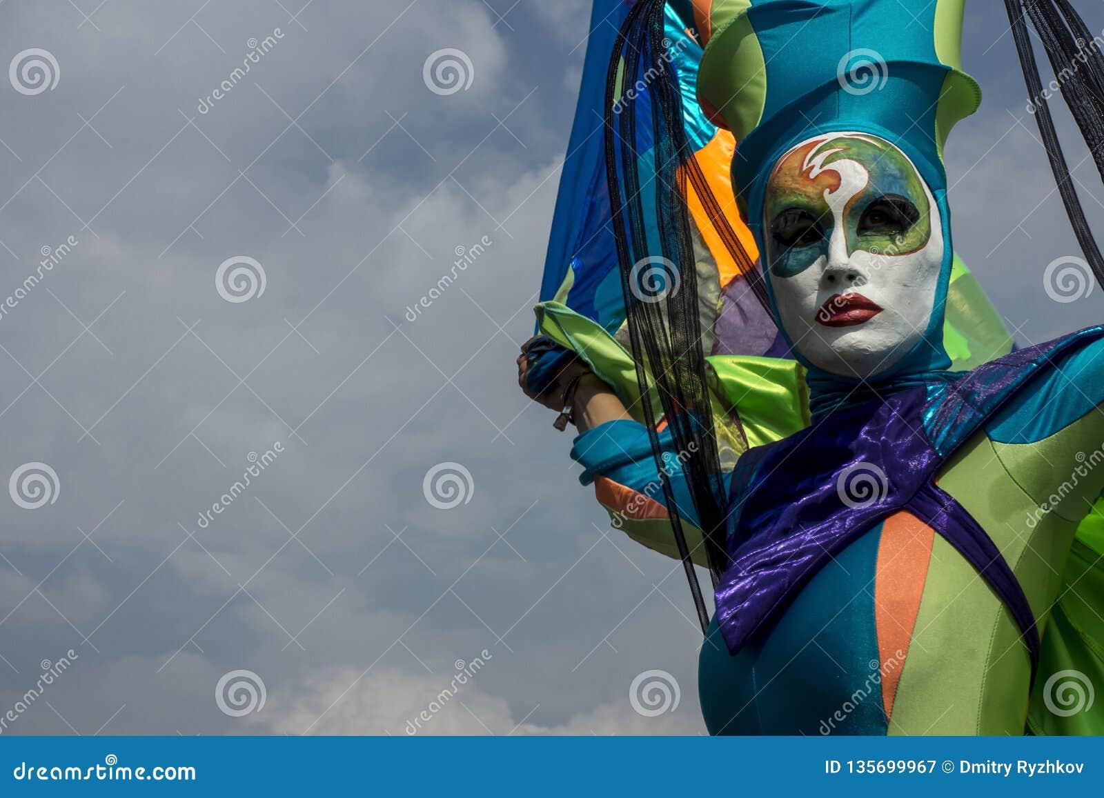 Akrobata w kolorowej masce w niebieskim niebie