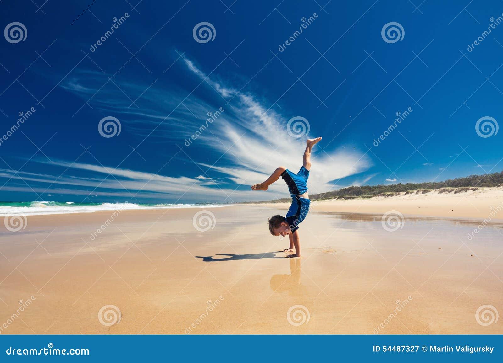 Akrobatischer Junge, der Handstand auf dem Strand durchführt