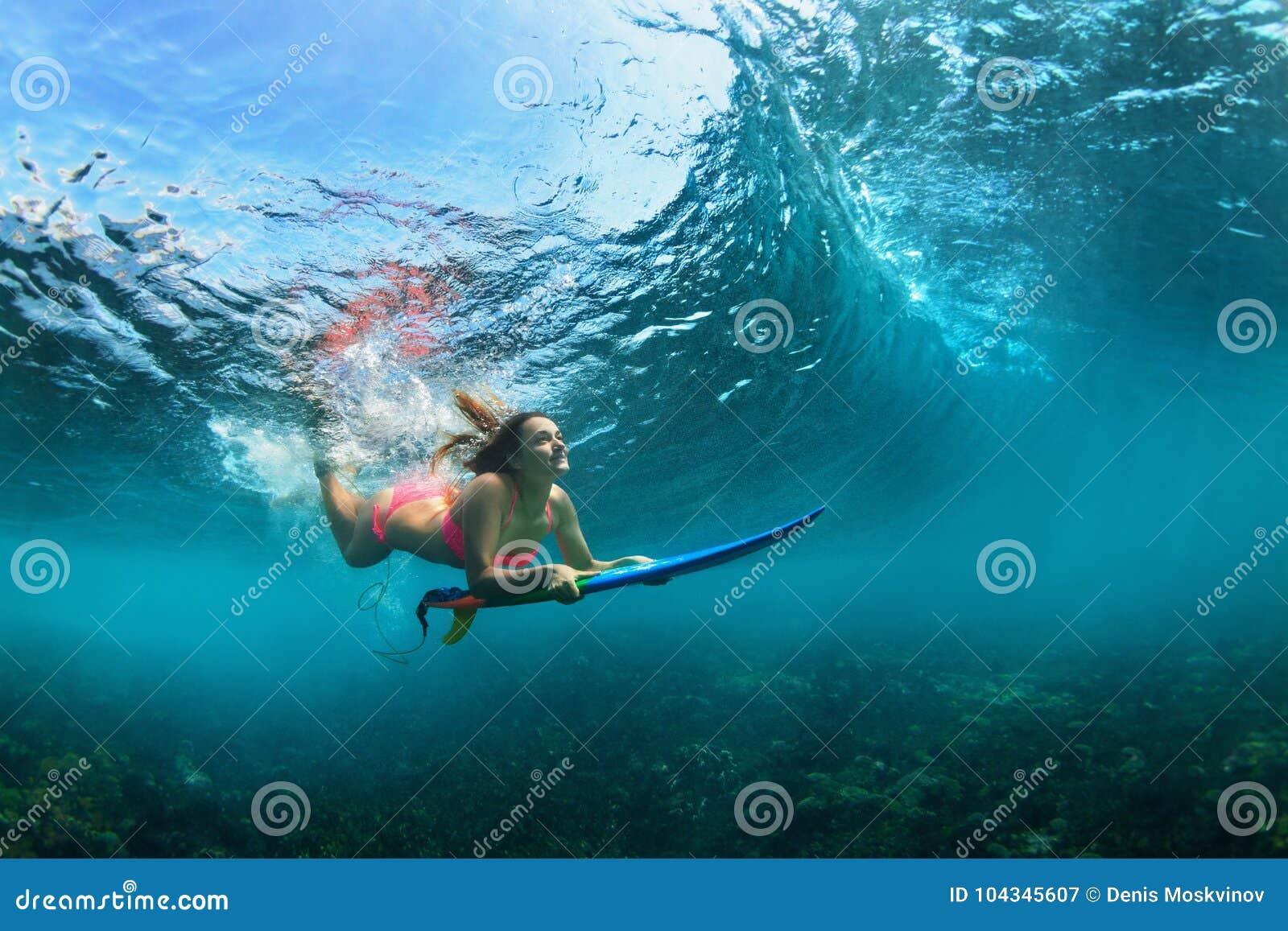 Aktiv flicka i bikini i dykhandling på bränningbräde
