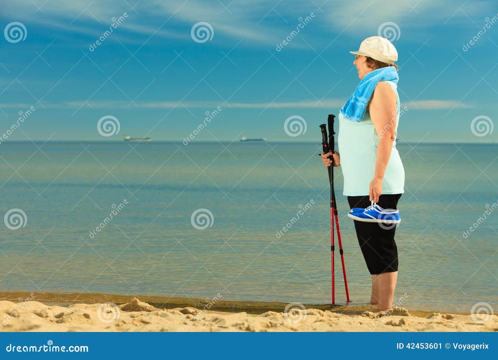 Aktive Frau älterer Nordic, der auf einen Strand geht