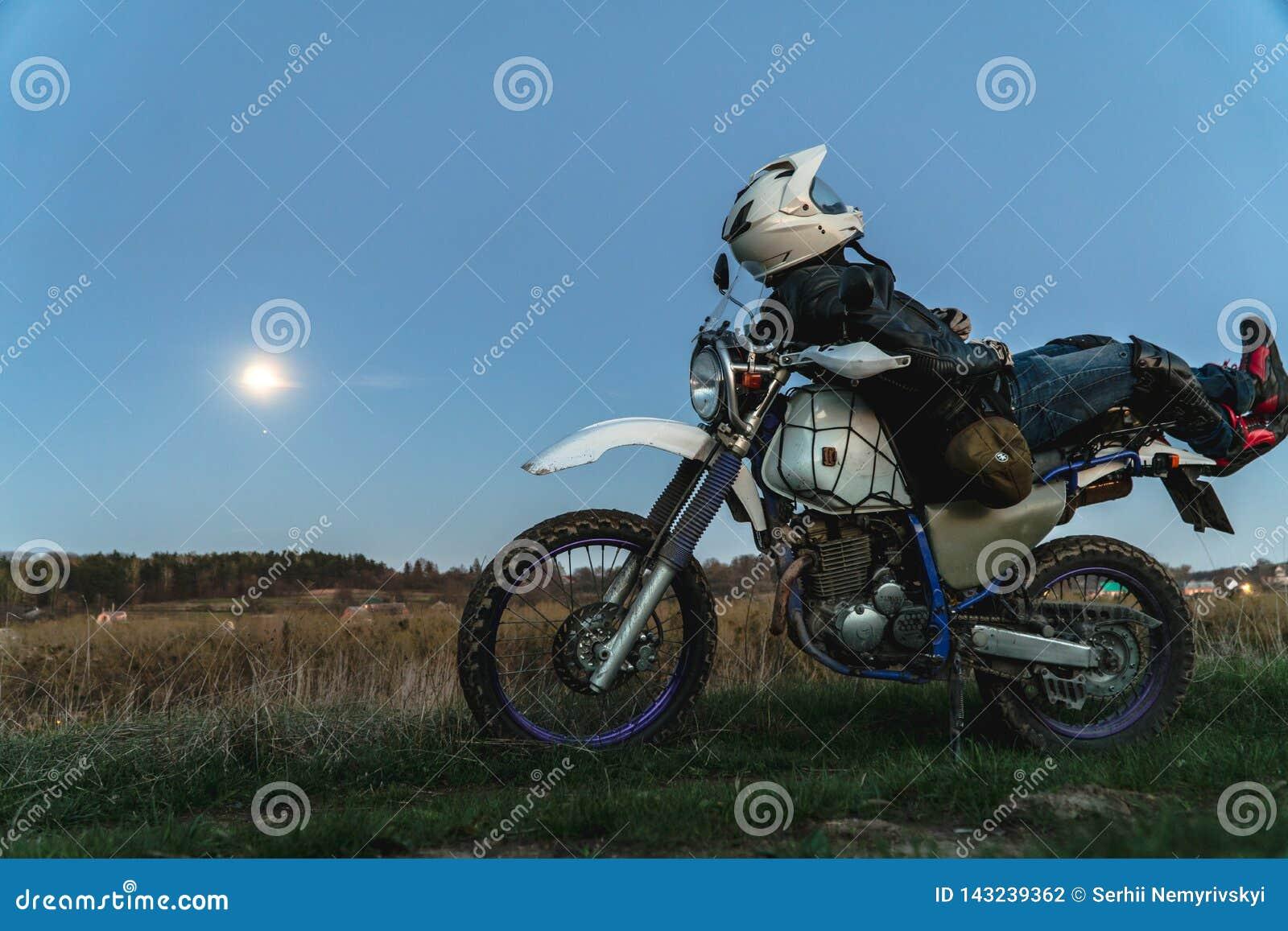 Aktive Lebensart, enduro Motorrad, ein Kerl betrachtet die Sterne nachts und den Mond, Einheit mit Natur, der Geist des Abenteuer