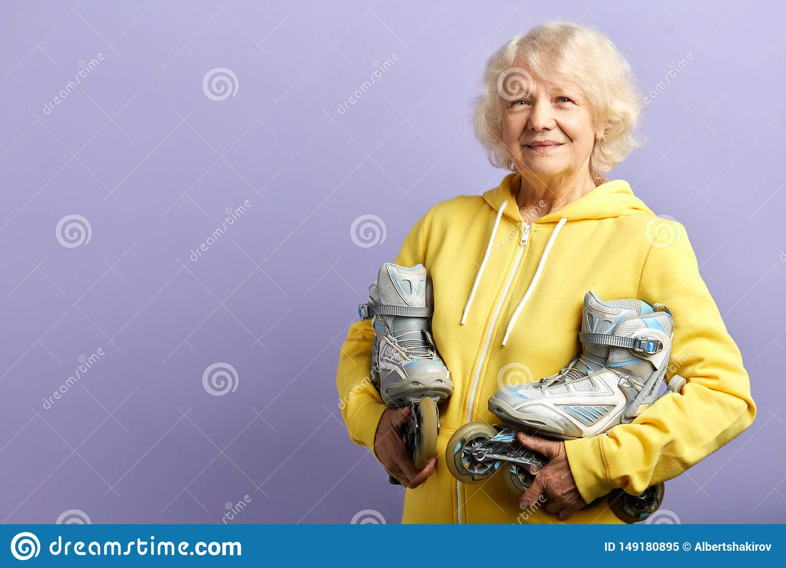 Aktive ?ltere Frau im gelben Sport Hoodiehalten l?uft zuhause aufwerfen Rollschuh
