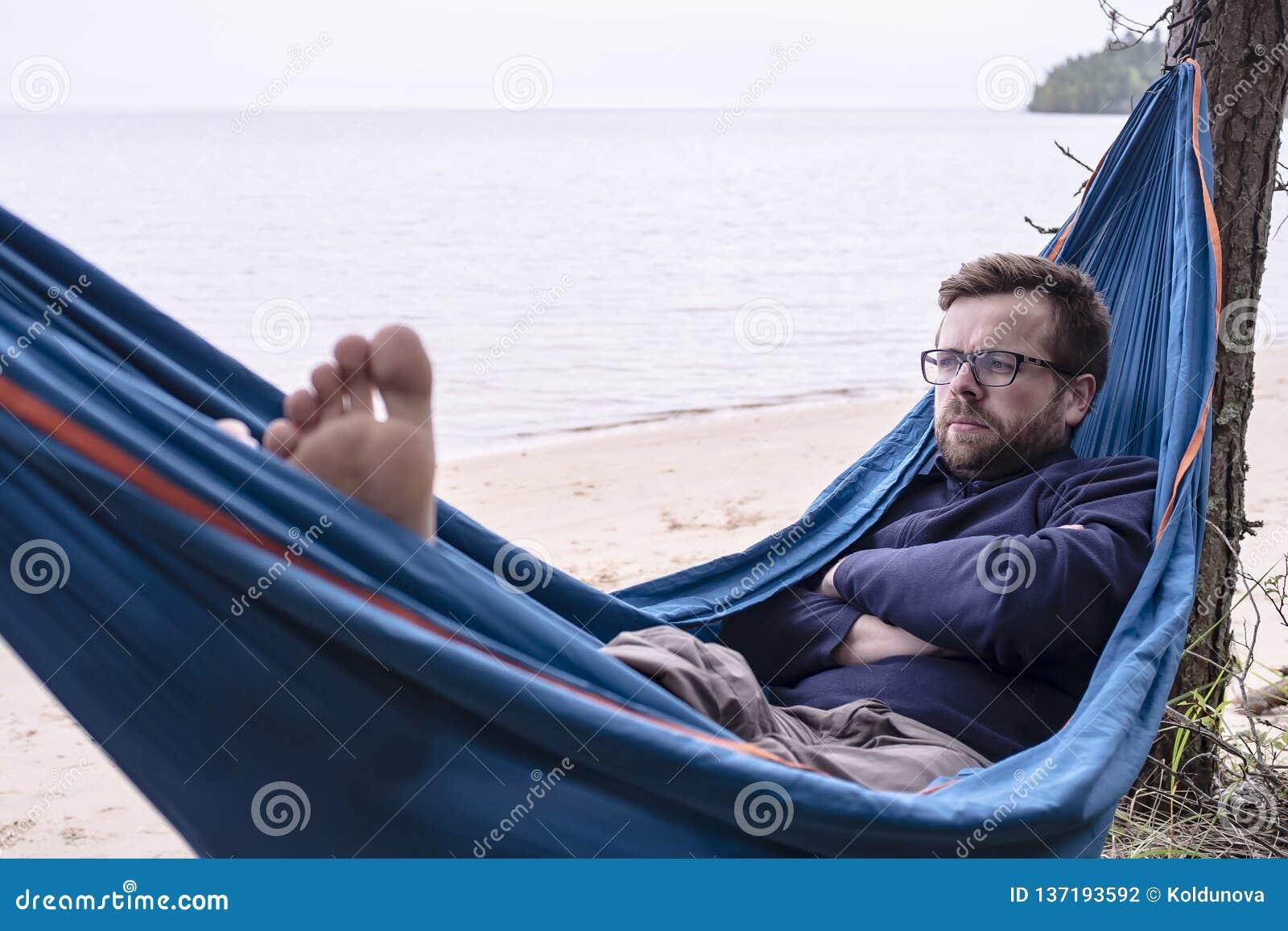 Aktiver Tourist ist ernste Träume und durchdacht, während er in einer Hängematte stillsteht