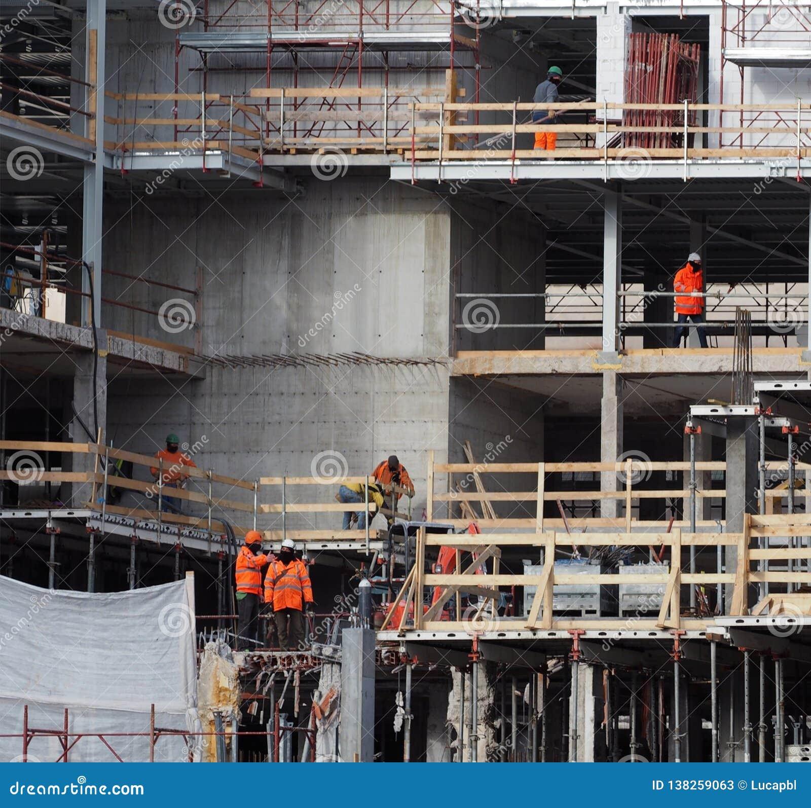 Aktivitet för konstruktionsplats Arbetare med arbete bär i en nybygge