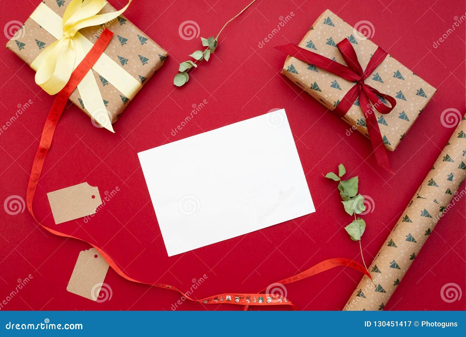 Aktuell weihnachtspakete för jul Gåvor som packas i hantverkpapper, bokstav för hälsningkort, pilbåge, torkade blommor på röd bak
