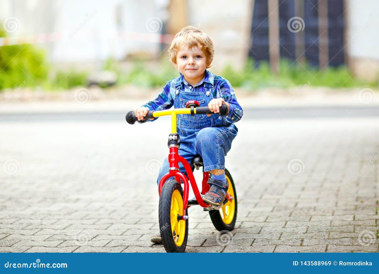 Aktywna blondynu dzieciaka chłopiec jedzie równowagę, ucznia bicykl w domowym ogródzie i rower w kolorowych ubraniach lub Berbeci