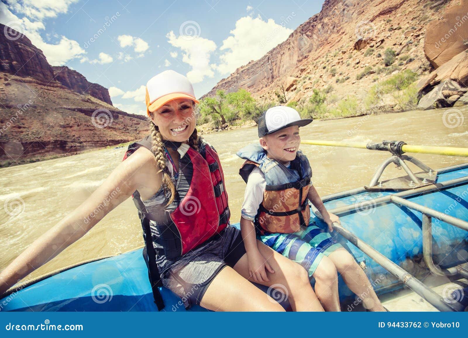 Aktywna młoda rodzina cieszy się zabawy whitewater flisactwa wycieczkę