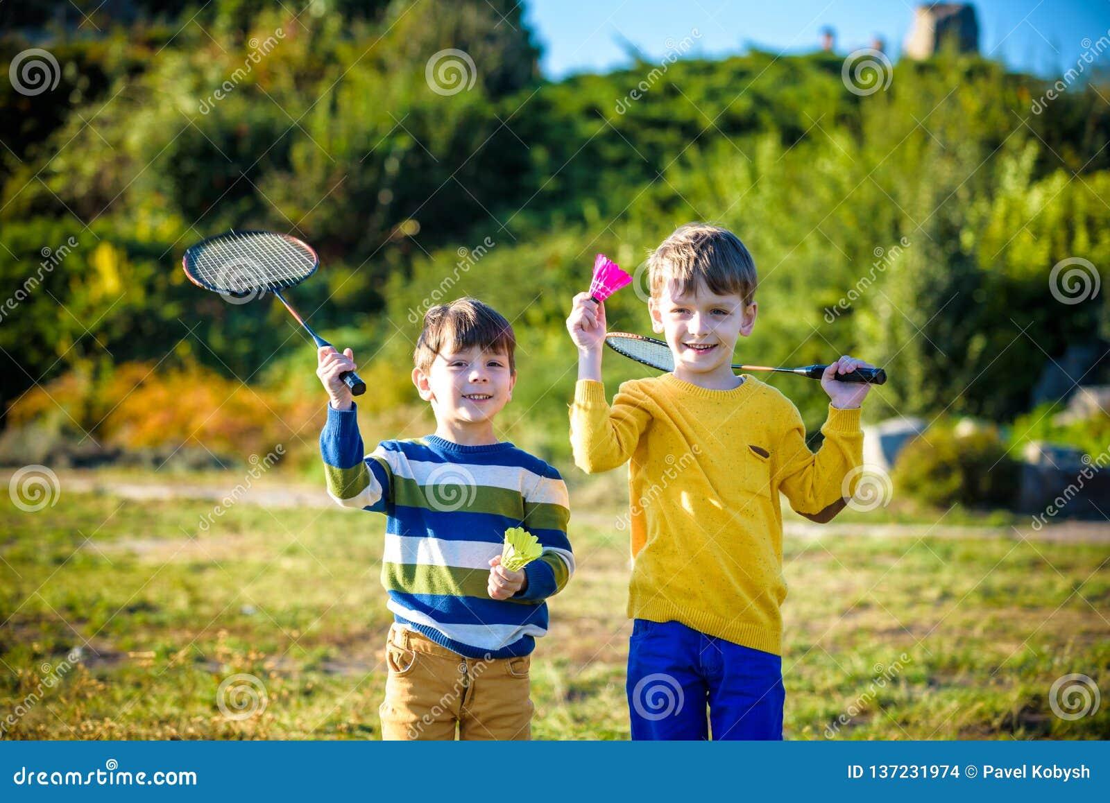 Aktywna preschool dziewczyna, chłopiec bawić się badminton w plenerowym sądzie w lecie i Dzieciak sztuki tenis Szkoła bawi się dl