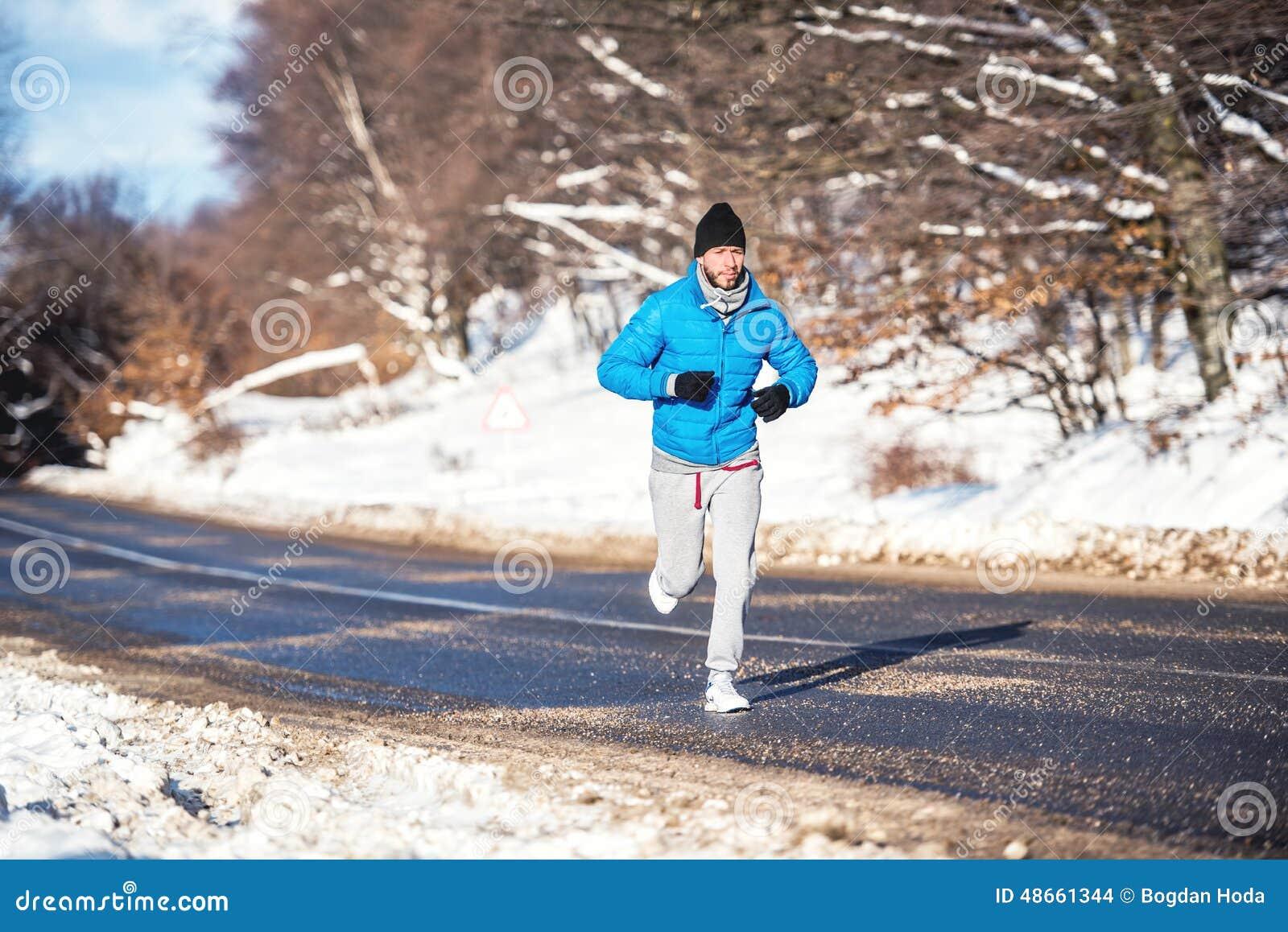 Aktywny mężczyzna jogging i biega podczas pogodnego zima dnia, Plenerowy pracujący out