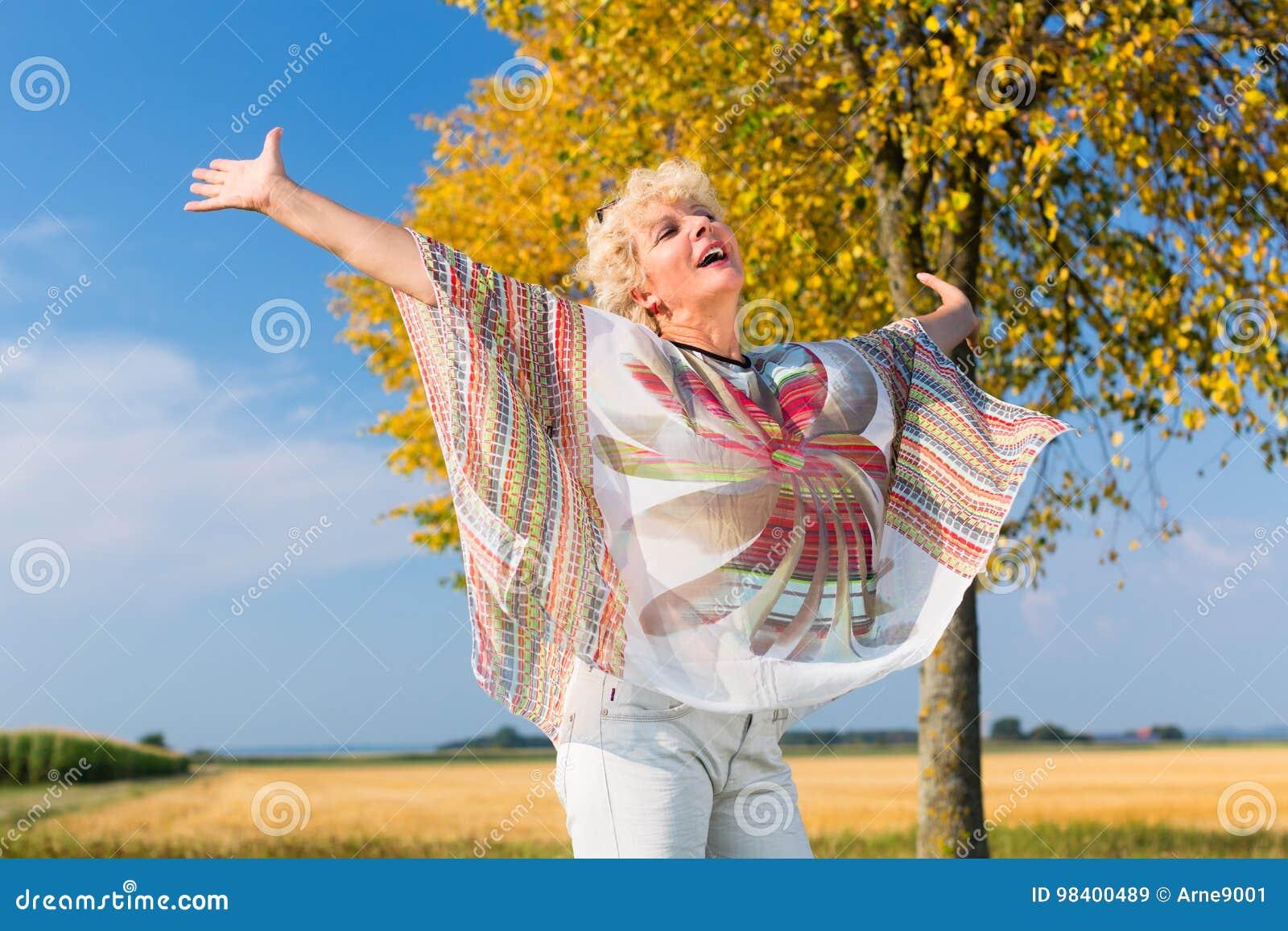 Aktywny starszy kobiety uczucie bezpłatny i szczęśliwy podczas gdy stojący outdoo