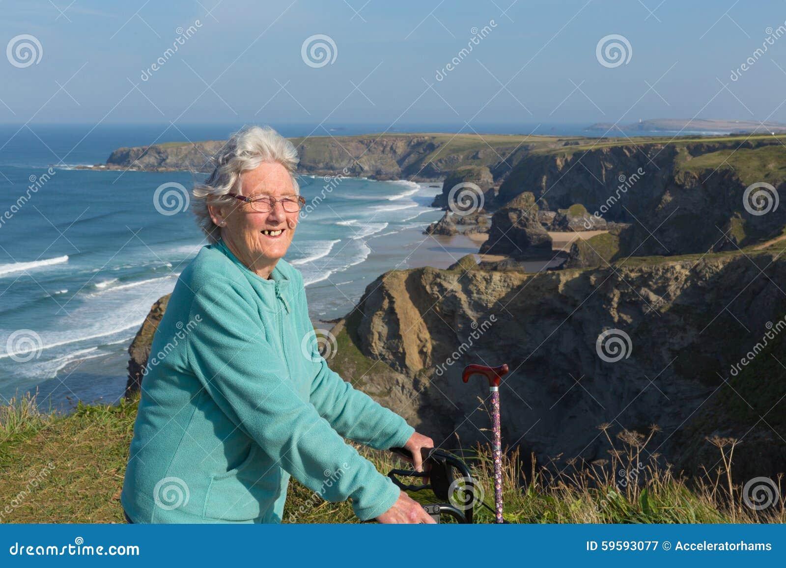 Aktywny szczęśliwy starszy żeński emeryt w lata osiemdziesiąte z ruchliwość ramowym i chodzącym kijem piękną brzegową sceną
