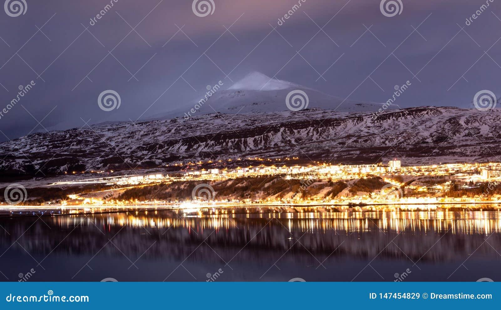 Akureyri, света города Исландии во время голубых часов с фоном гор льда