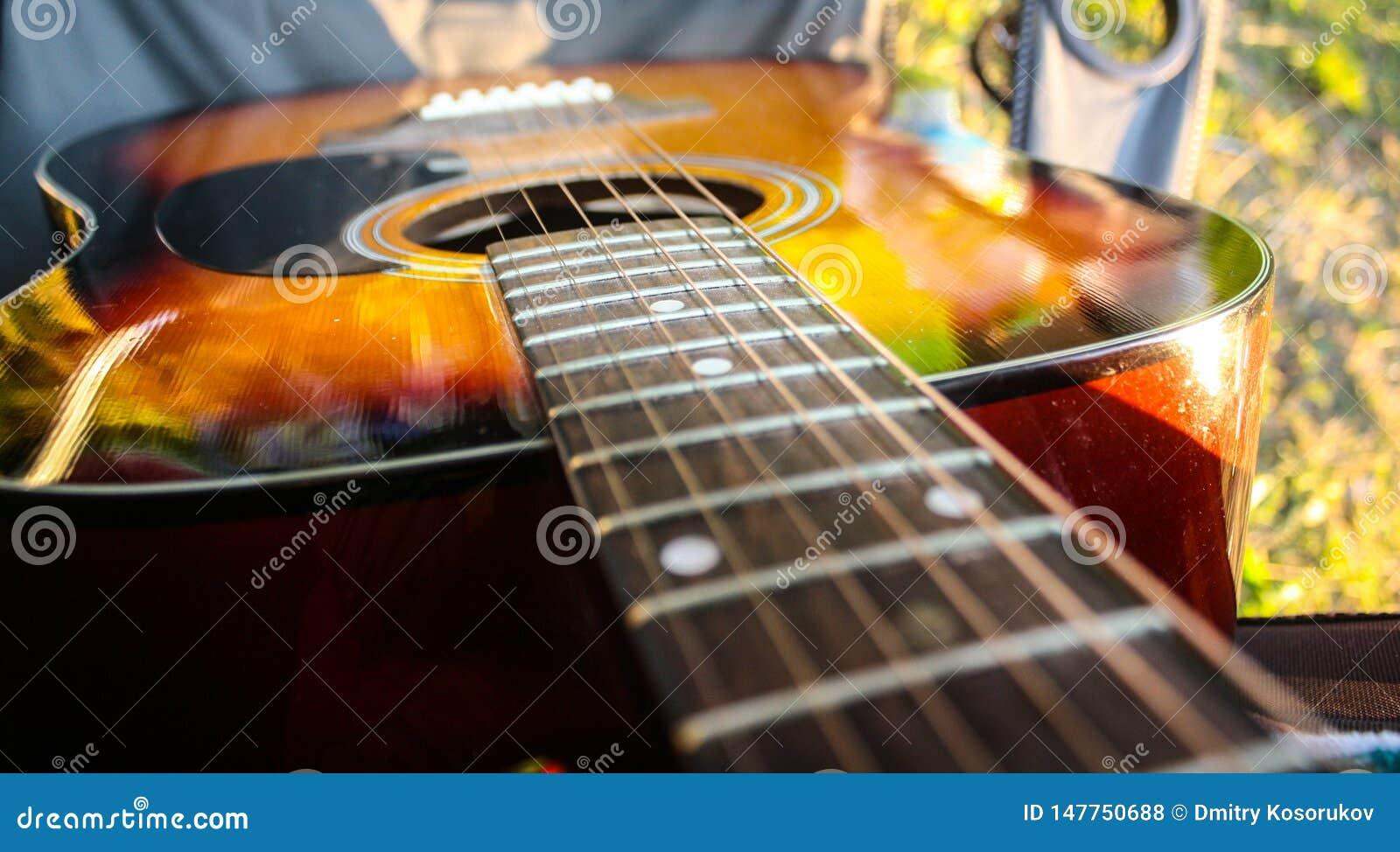 Akustyczna pomarańczowa gitara na campingu