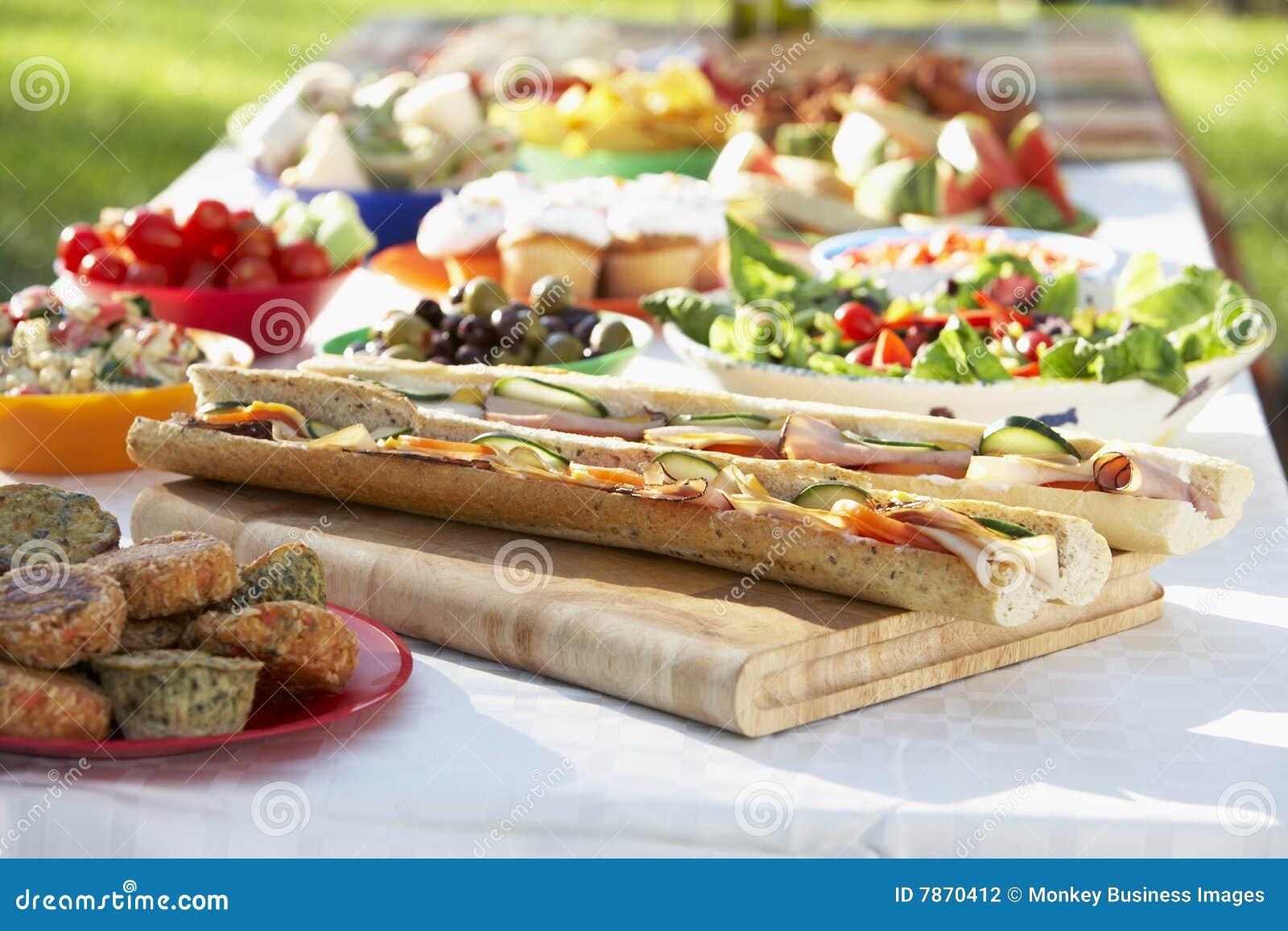 Al-Fresko, das speist, wenn die Nahrung auf Tabelle ausgebreitet ist