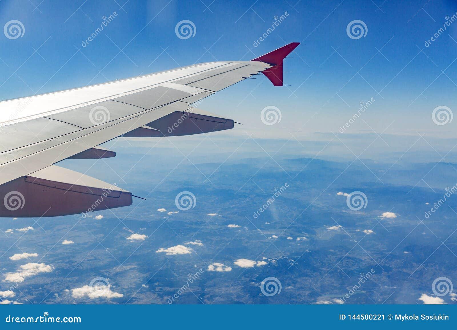 Ala de aviones en las nubes, moscas en el fondo de la ciudad
