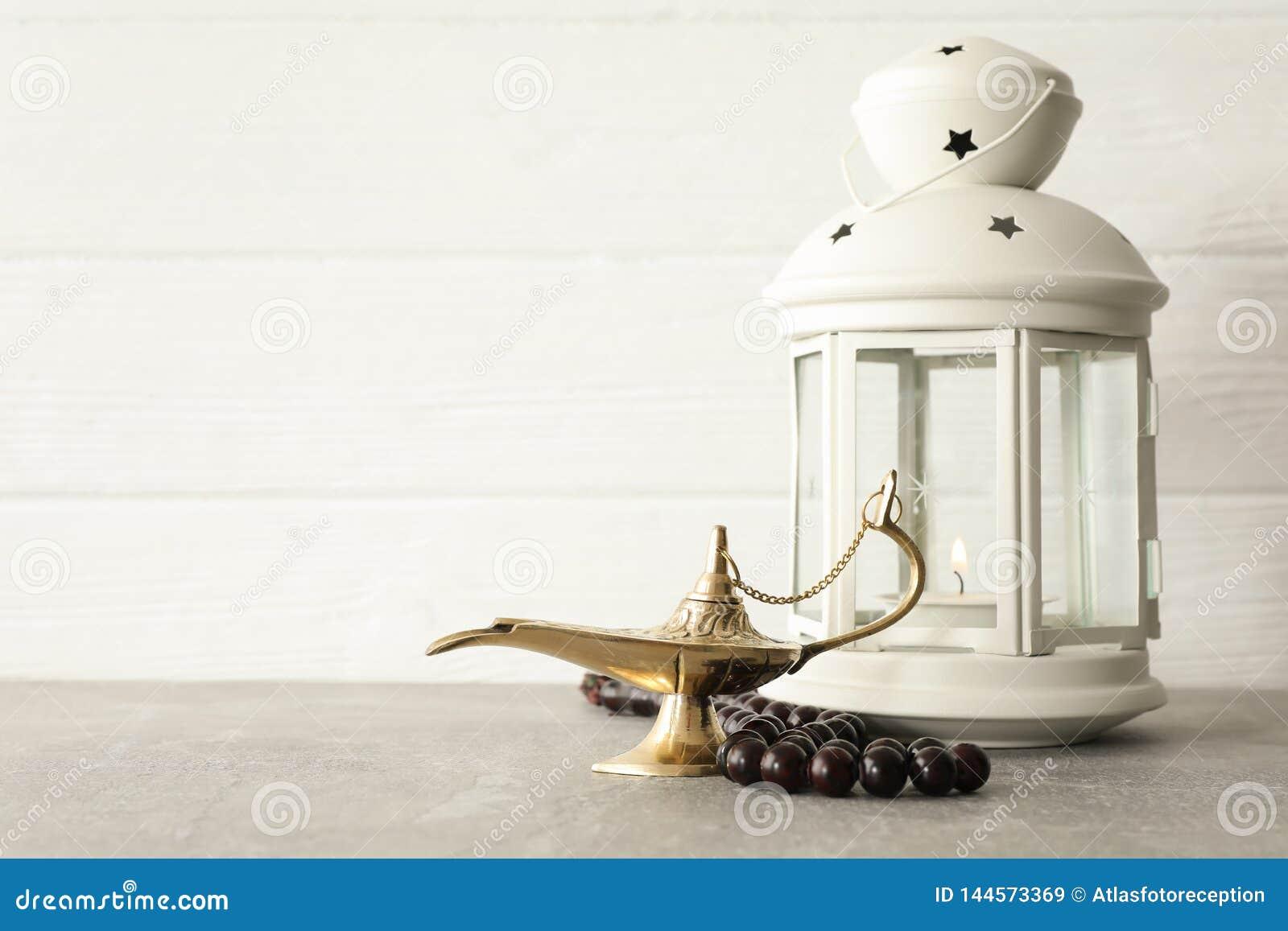 Aladdin Lamp mágico com grânulos de oração e lanterna da ramadã na tabela cinzenta