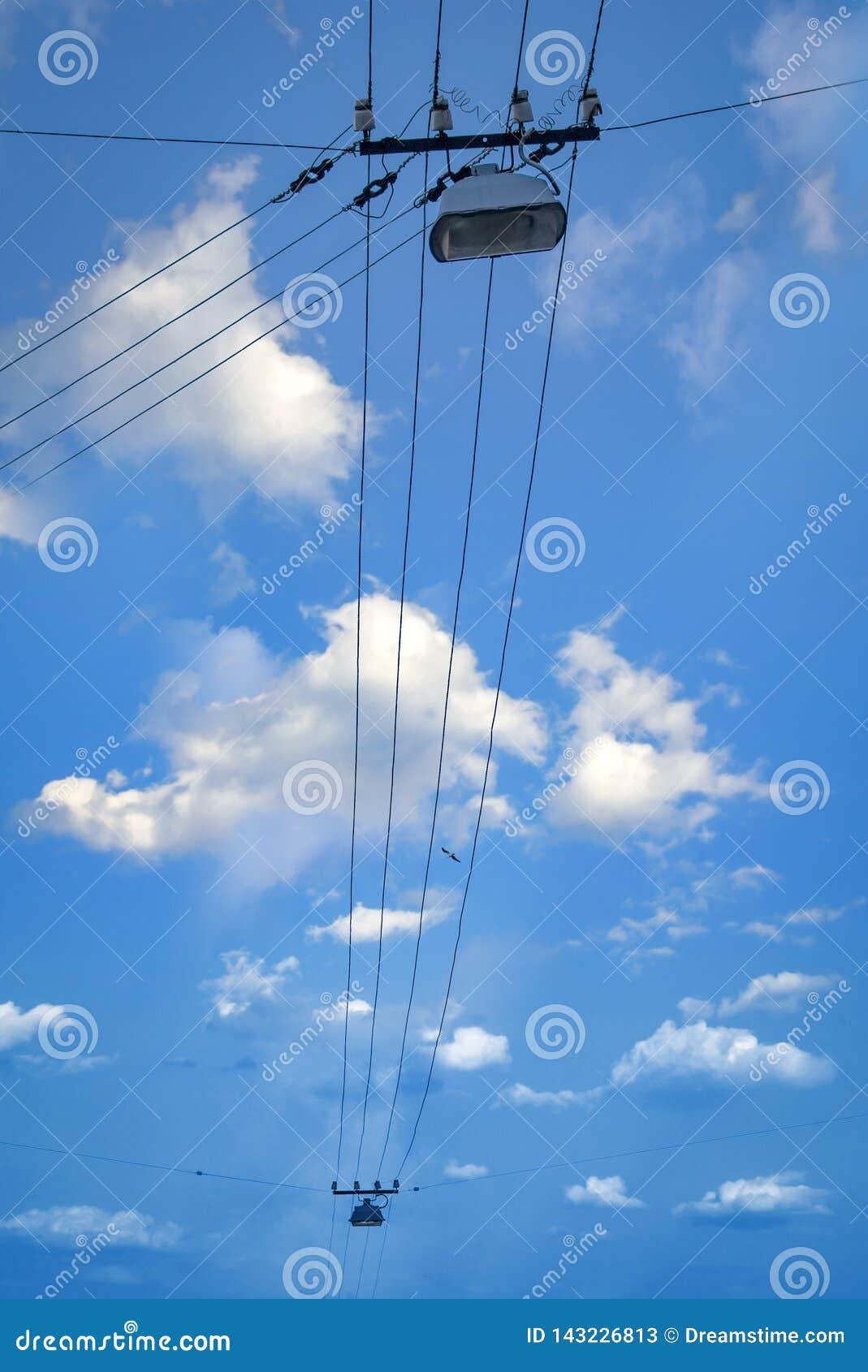 Alambres eléctricos con las luces de calle en fondo del cielo azul