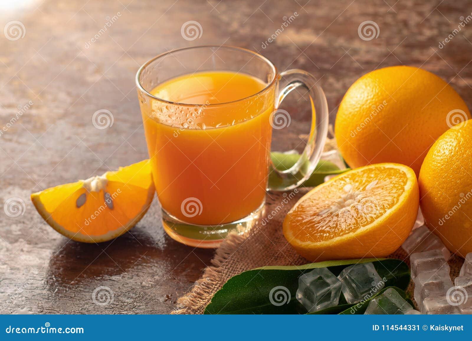 Alaranjado fresco e um vidro do suco de laranja em um backg de madeira da tabela