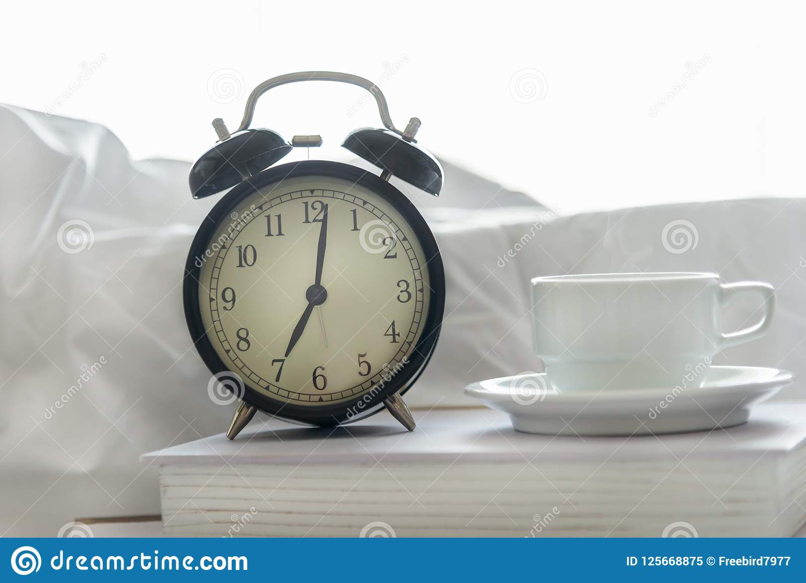 Alarm Clock With Book On Bed In Morning