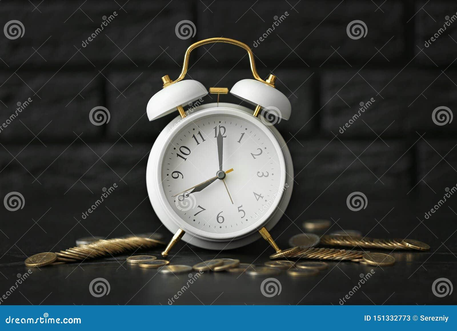 Alarm clock with coins on dark table