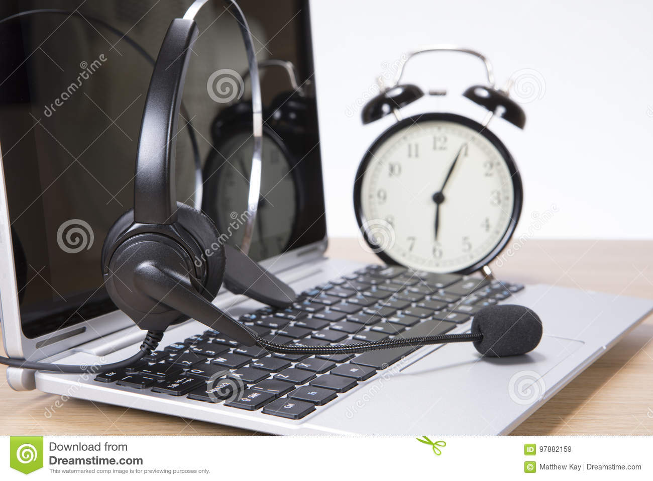 Alarm clock and headset on a laptop computer