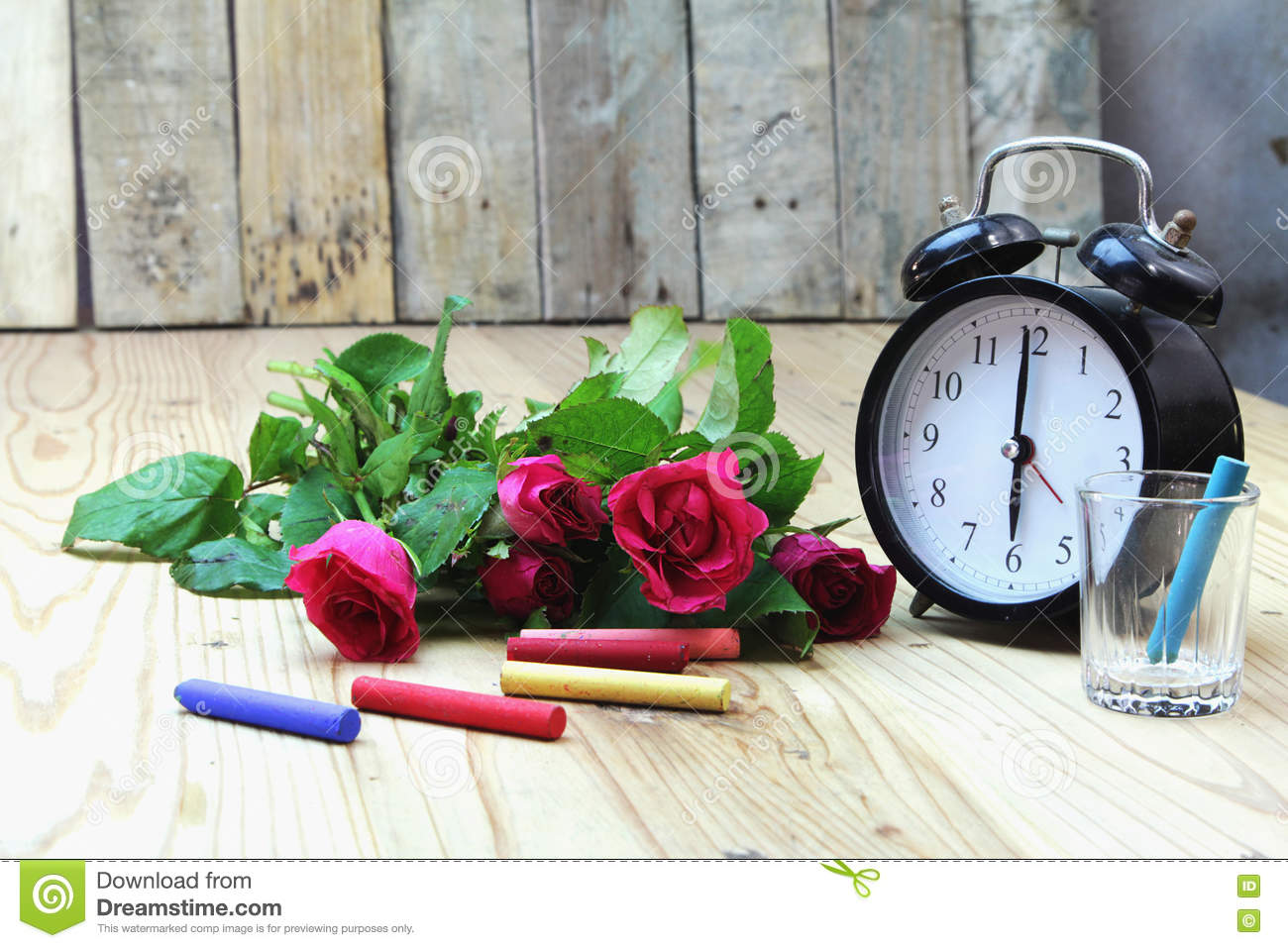 Alarm clock with roses on old wood