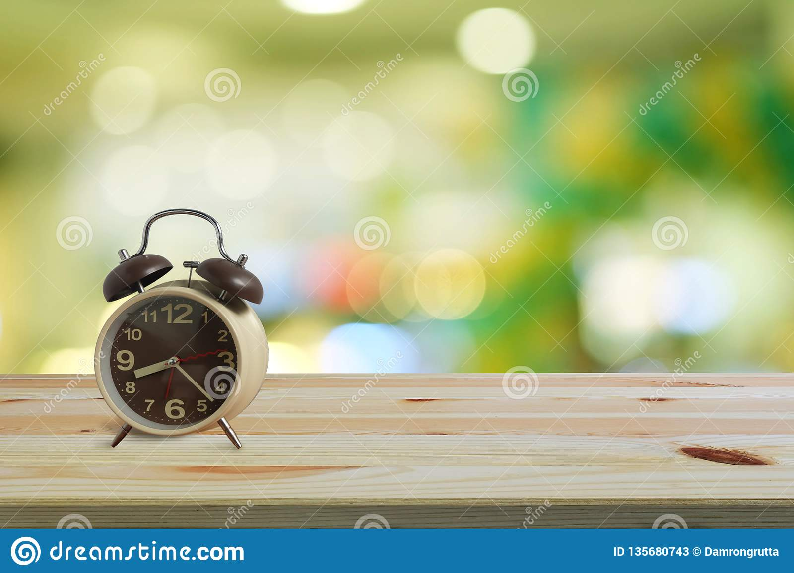 Alarm clock on wooden floor and green bokeh background with copy space, Morning wake up is bright air of nature