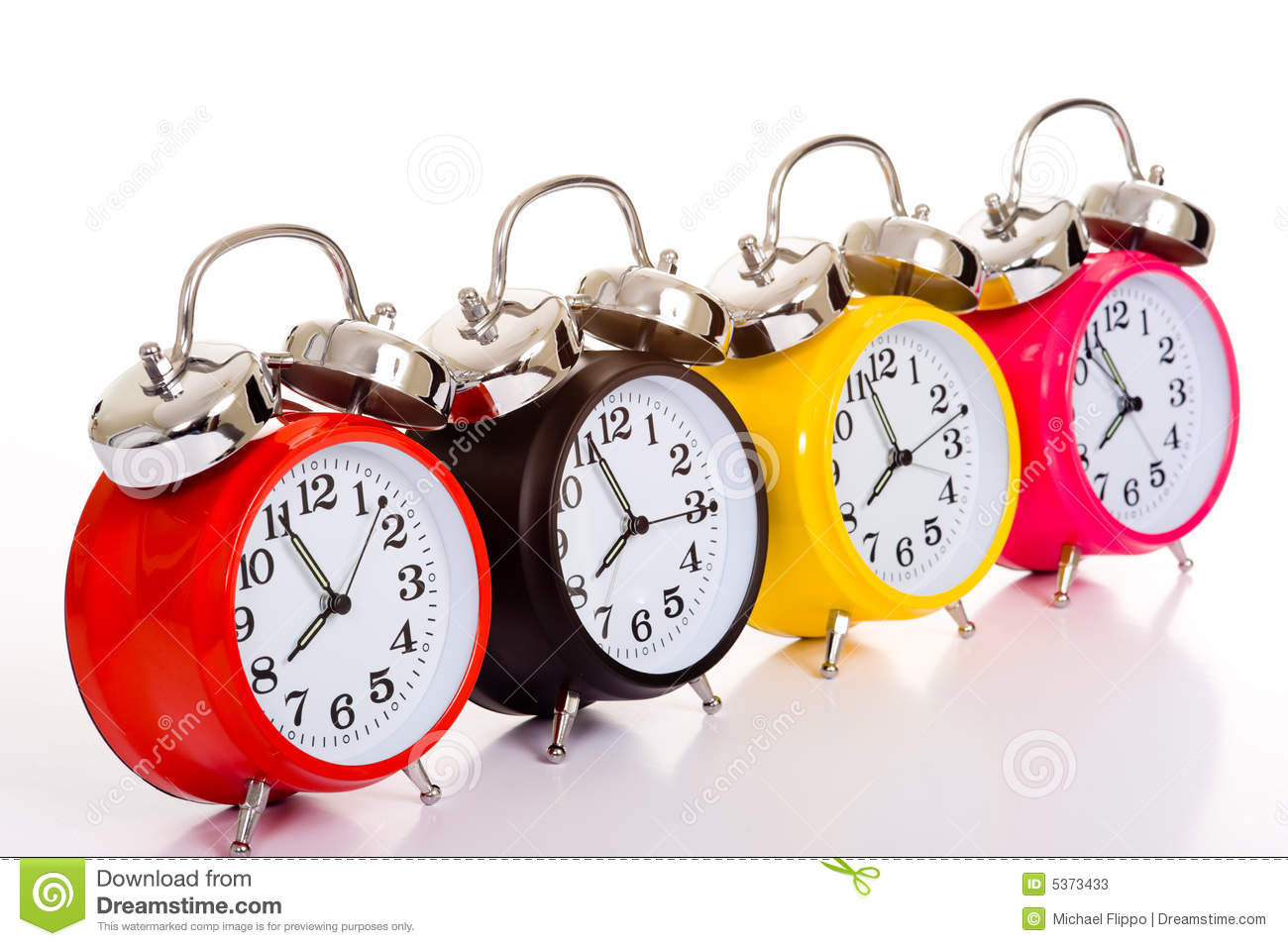 ... colored traditional alarm clocks thrown on a white background