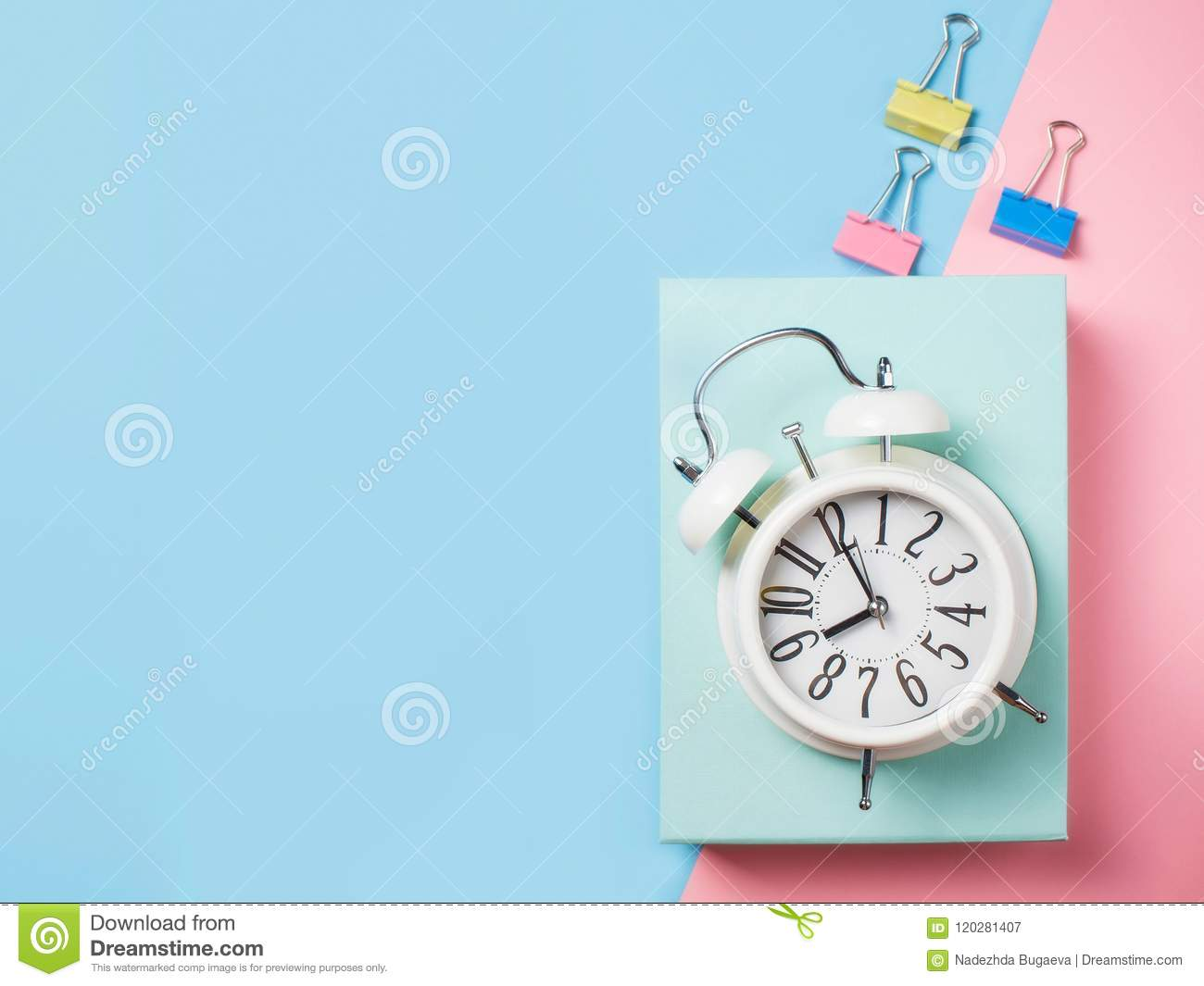 Alarm with supplies on color block background. Pastel minimalism
