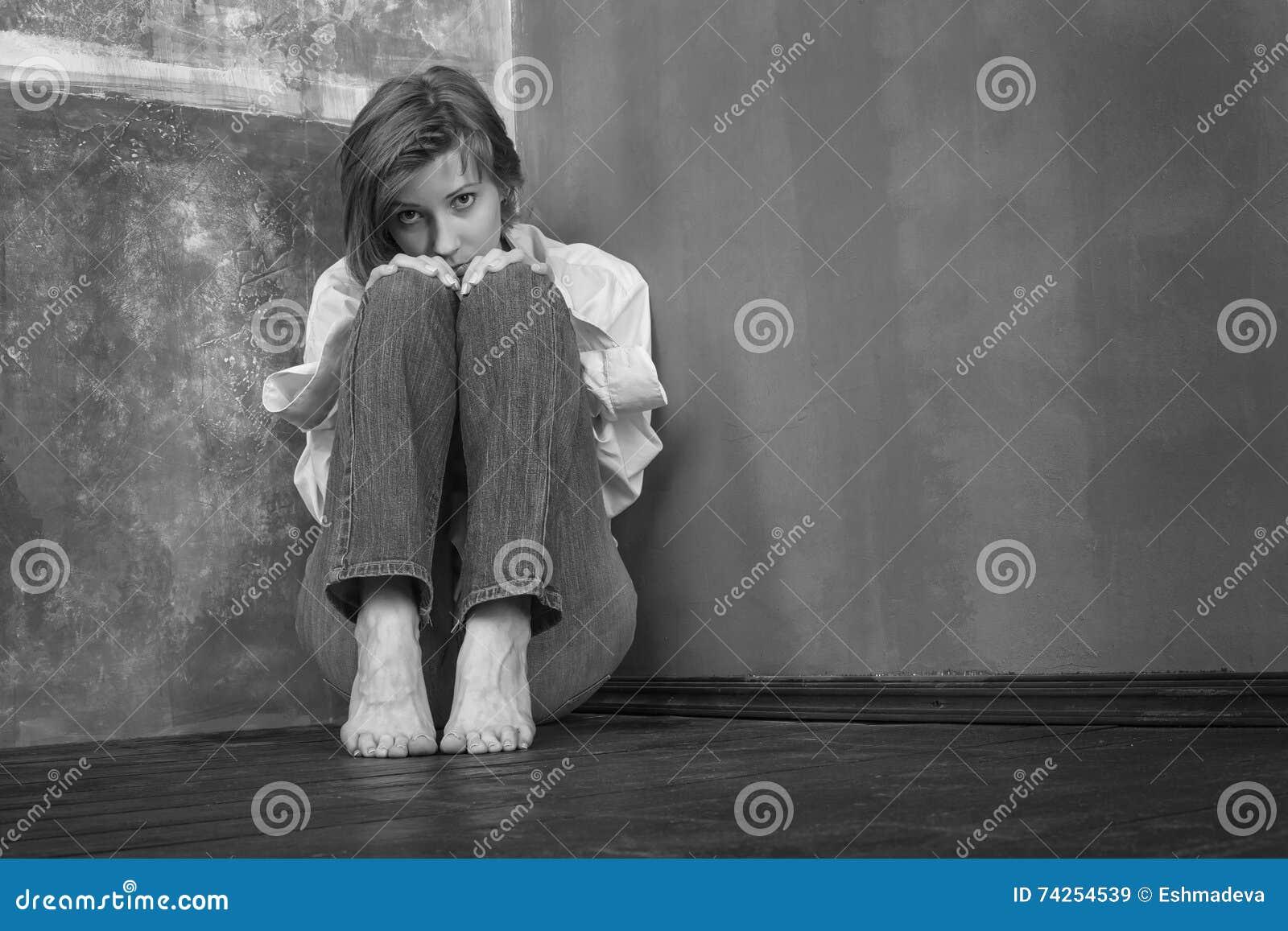 Alarmująca kobieta, siedzi na podłoga