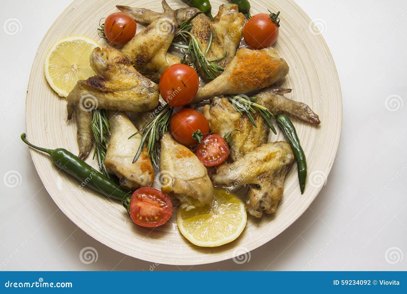 Alas y piernas calientes de pollo con las verduras
