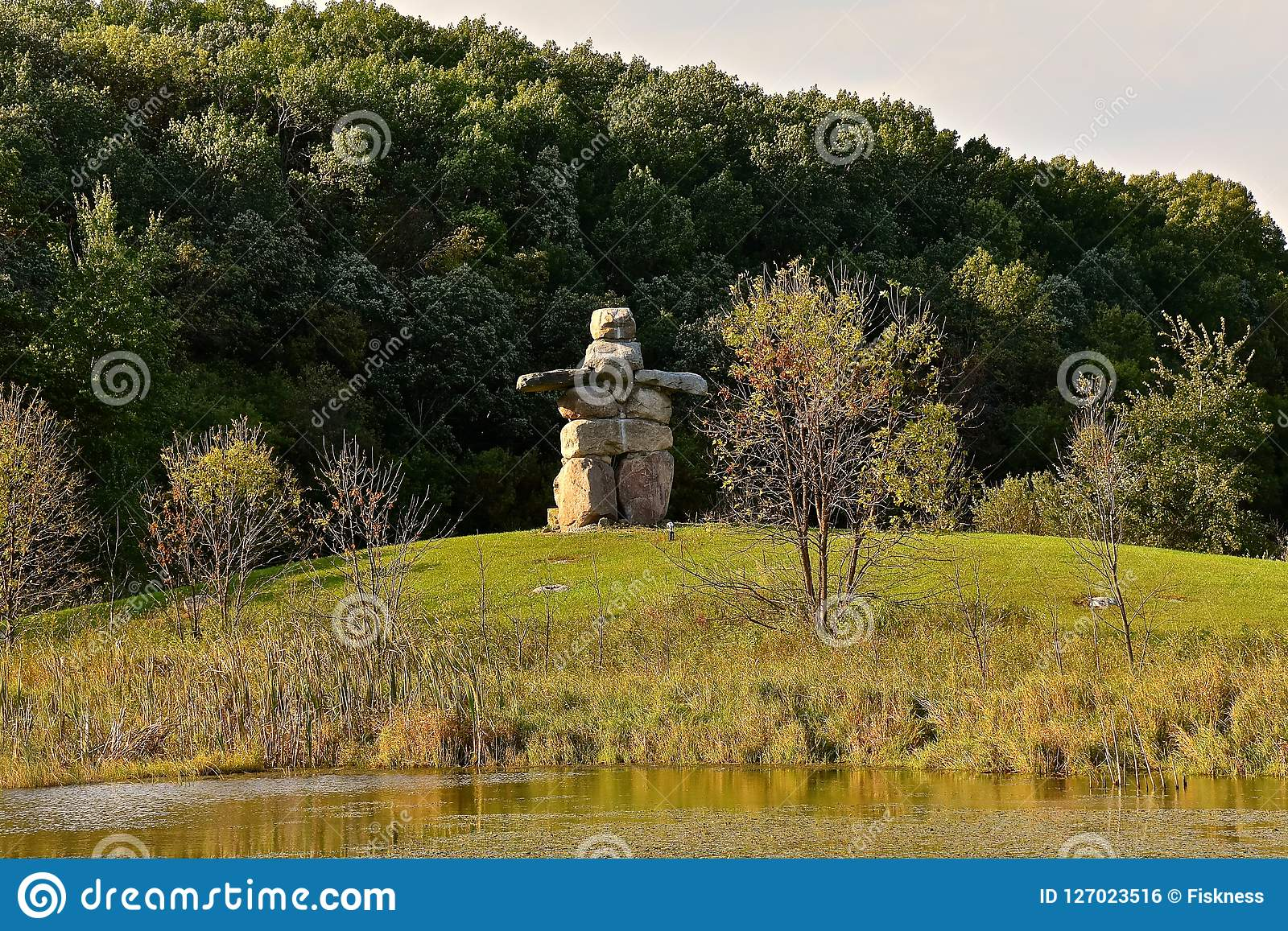 A Inukshuk located along a hill by a body on water and woods