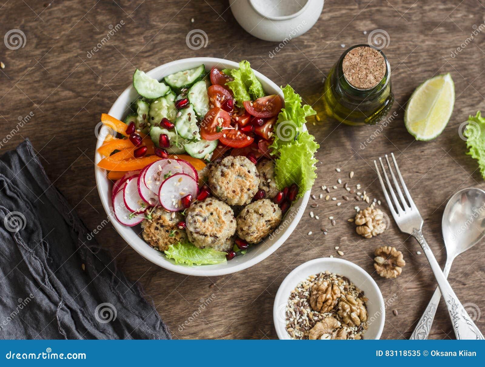 Albóndigas cocidas y ensalada vegetal en una tabla de madera, visión superior de la quinoa Cuenco de Buda Sano, dieta, concepto v