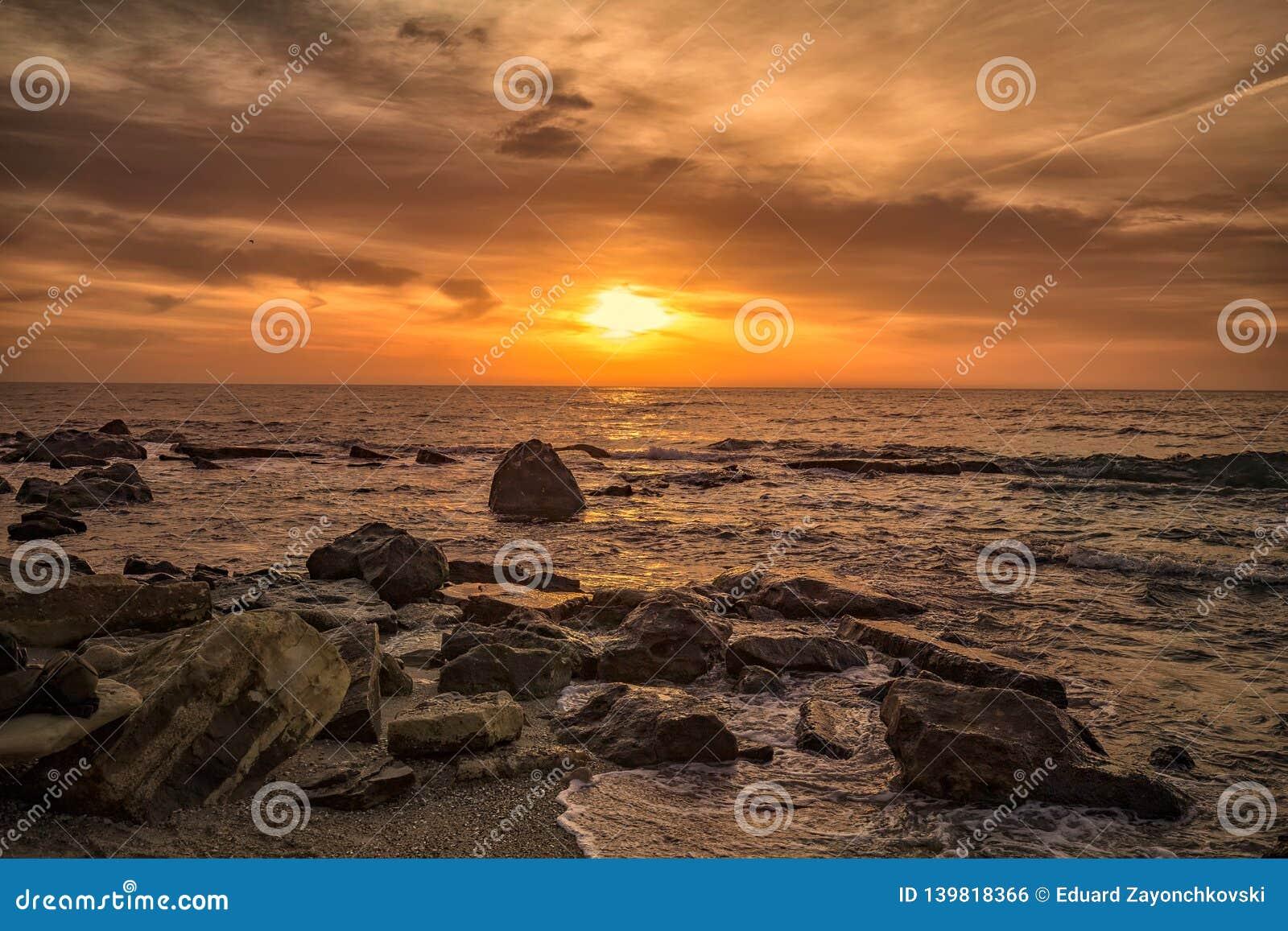 Alba sopra il mare con la costa rocciosa