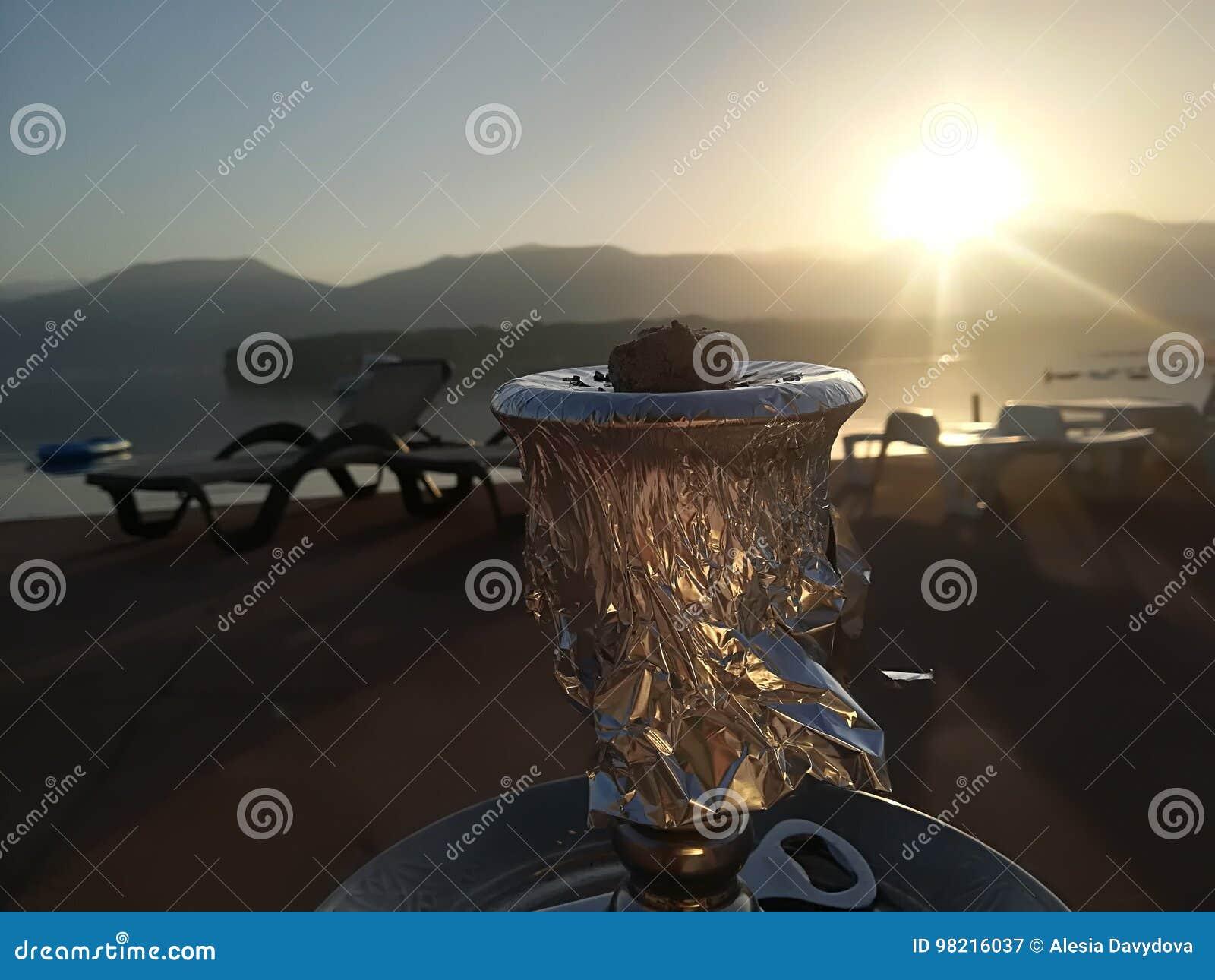 Alba variopinta sulla spiaggia contro lo sfondo del mare e delle montagne