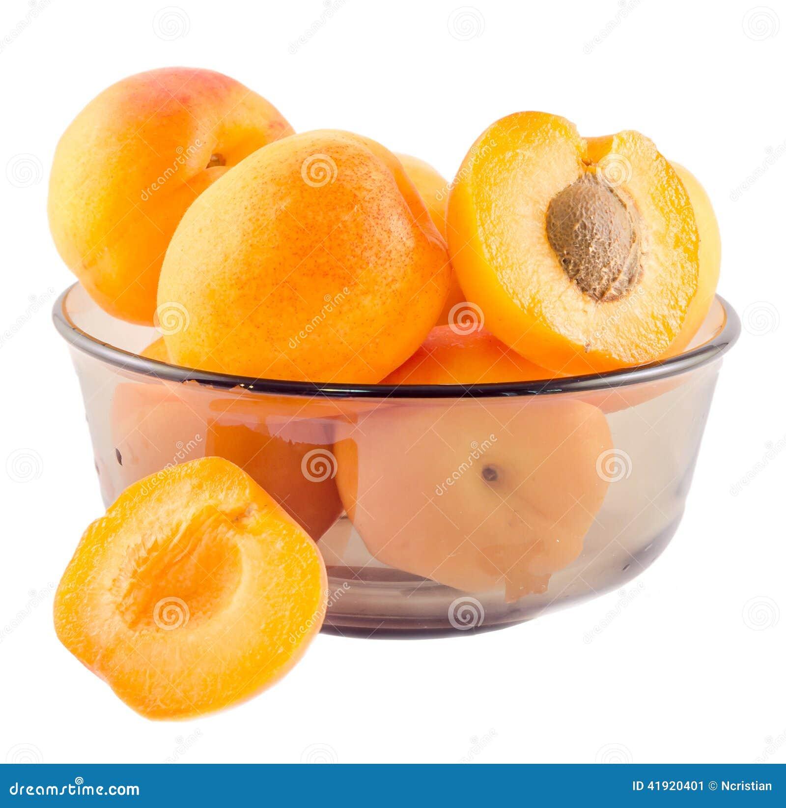 Albaricoques amarillo-naranja, medio albaricoque con la pipa, en un cuenco transparente marrón