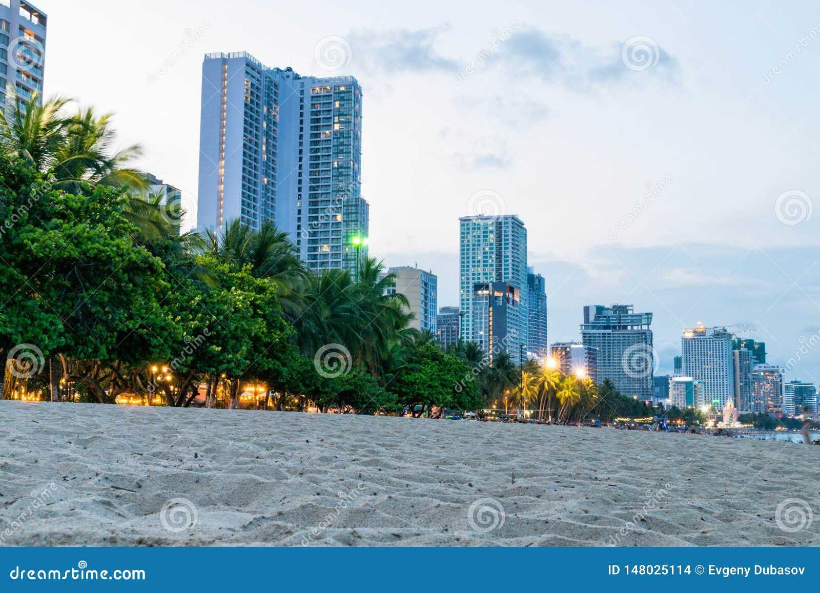 Alberi e costruzioni tropicali degli hotel sulla spiaggia nel crepuscolo