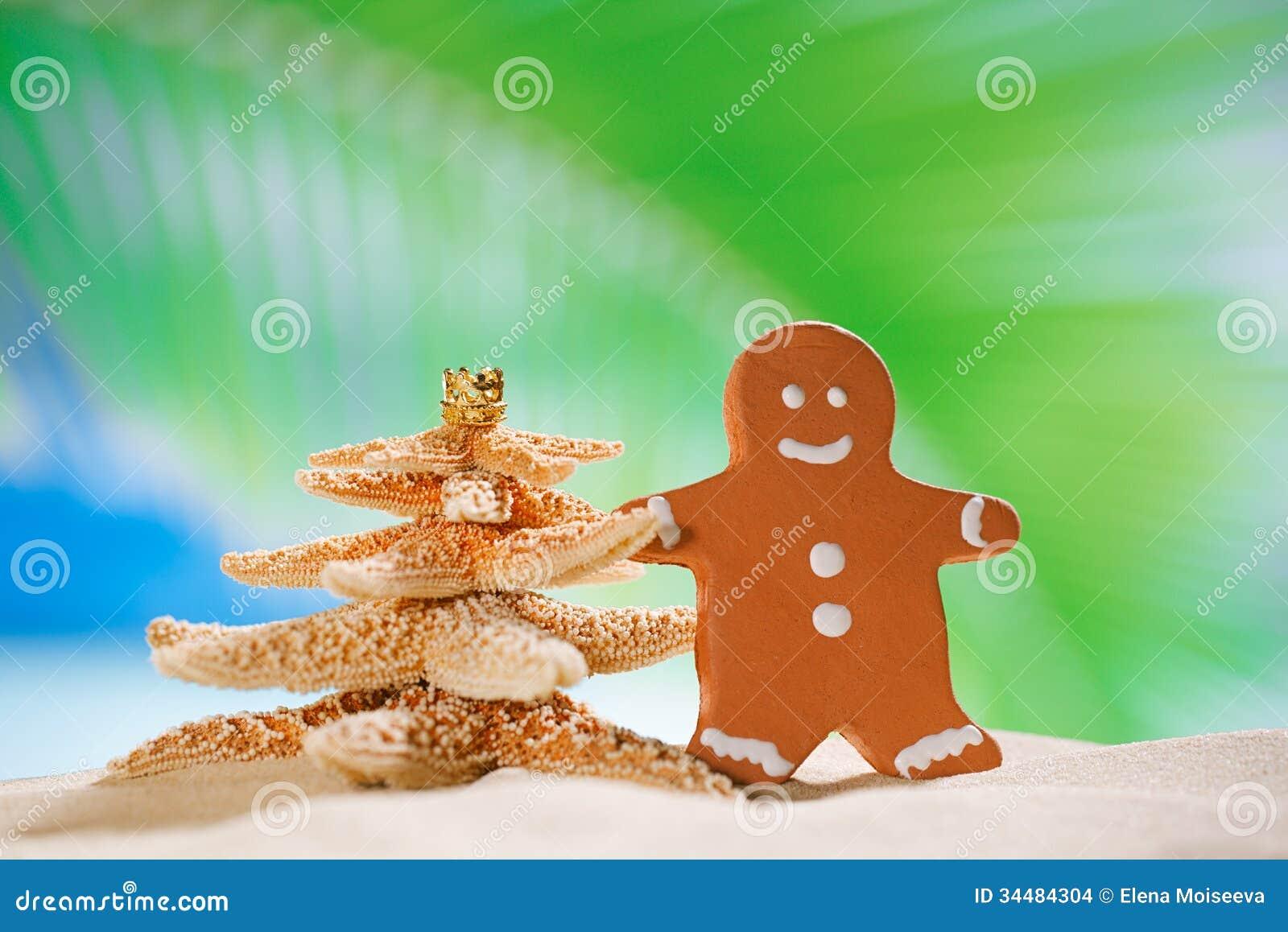 Albero di Natale dell uomo e delle stelle marine di pan di zenzero sulla spiaggia con il seasca