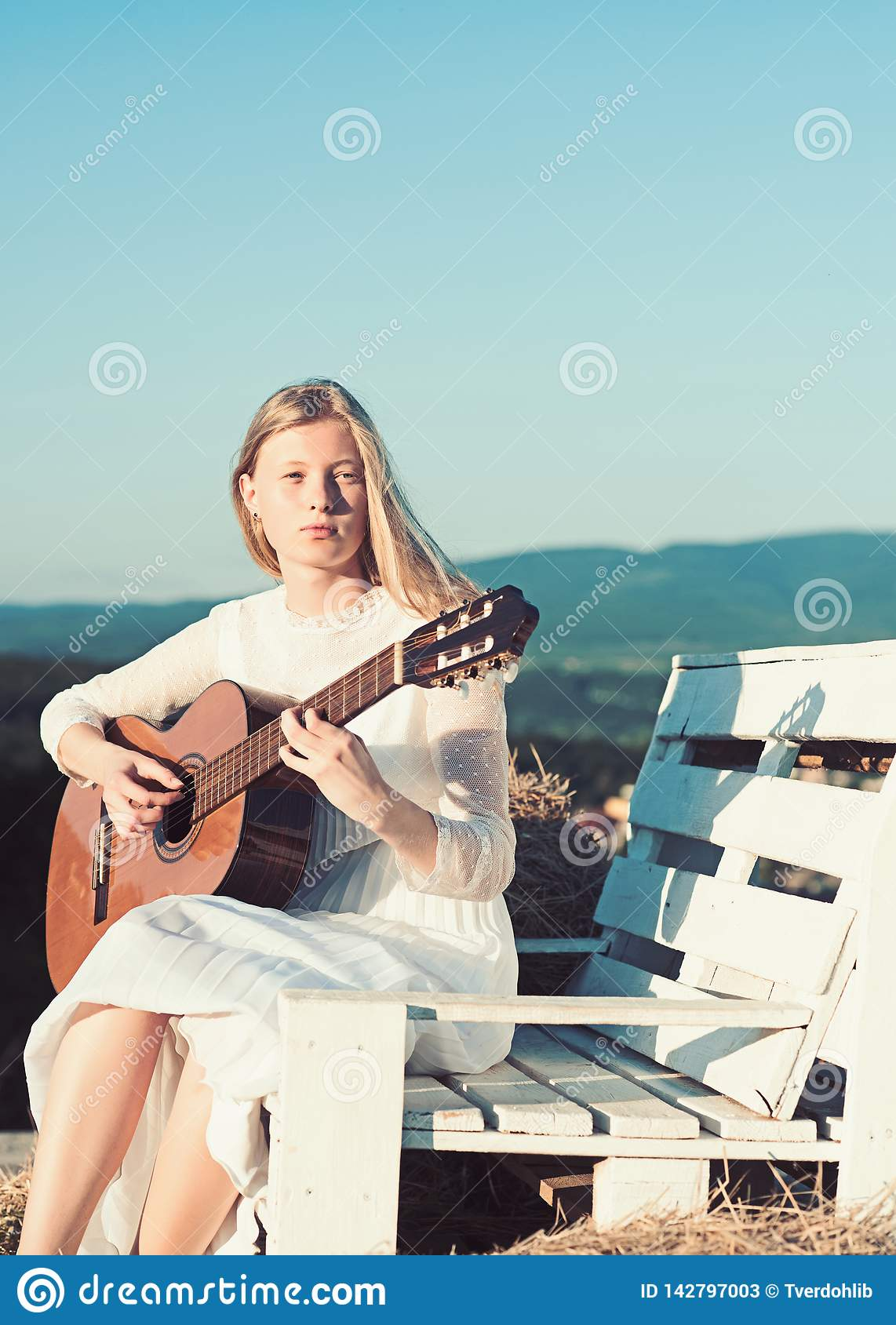 Albino girl hold acoustic guitar, string instrument. Fashion musician in white dress on sunny nature. Sensual woman play