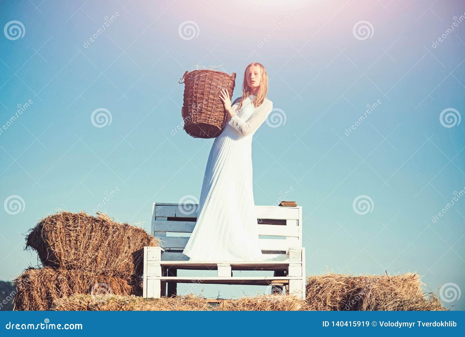 Albinos dziewczyny chwyta łozinowy kosz z sianem na pogodny plenerowym Kobiety panna młoda w ślubnej sukni na drewnianej ławce Se
