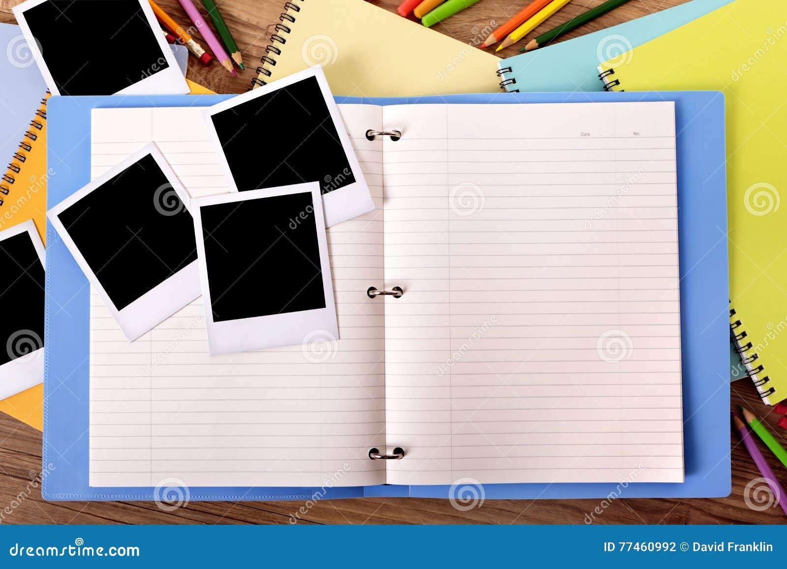 Album di foto aperto con parecchie strutture in bianco della stampa della foto di stile della polaroid