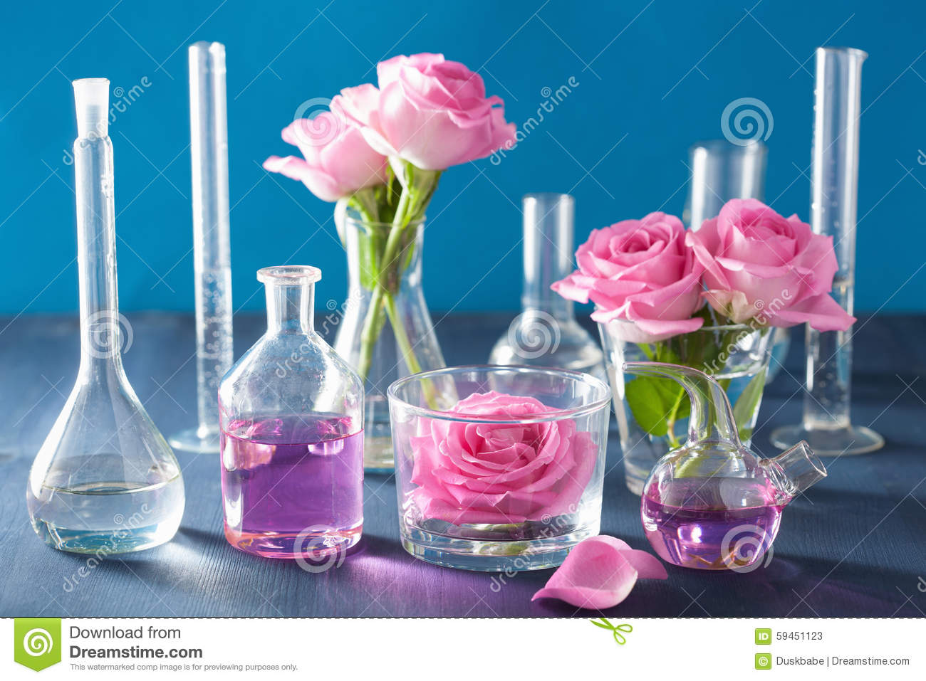 Alchemy and aromatherapy set with rose flowers and chemical flas