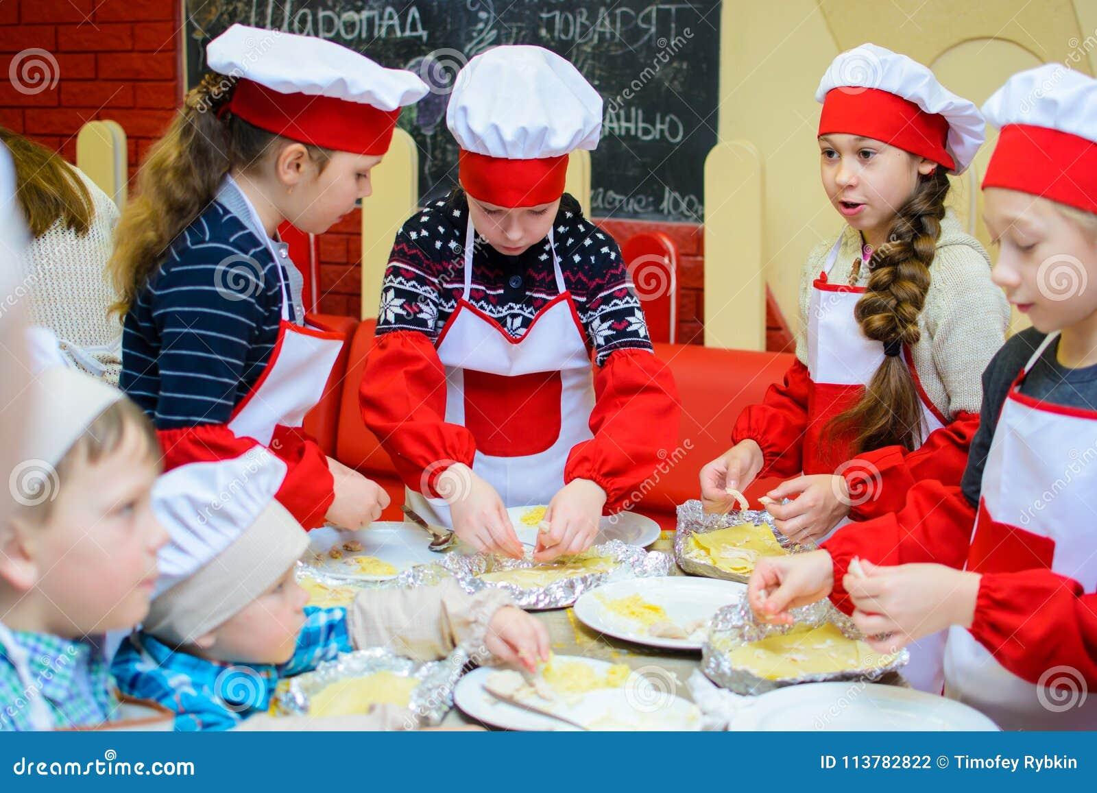 Alchevsk, Ουκρανία - 21 Ιανουαρίου 2018: Τα παιδιά υπό μορφή μαγείρων μαθαίνουν πώς να μαγειρεψουν το lasagna