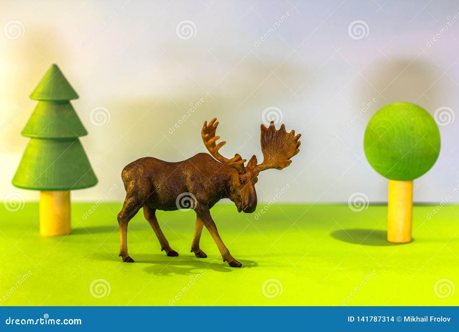 Alci del giocattolo in una foresta del giocattolo come un alce reale su un fondo luminoso dello studio con gli alberi di legno Gi