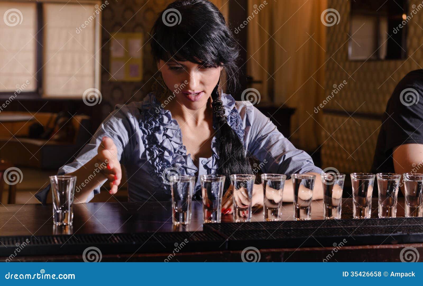 Alcoólico fêmea que traga uma fileira dos tiros