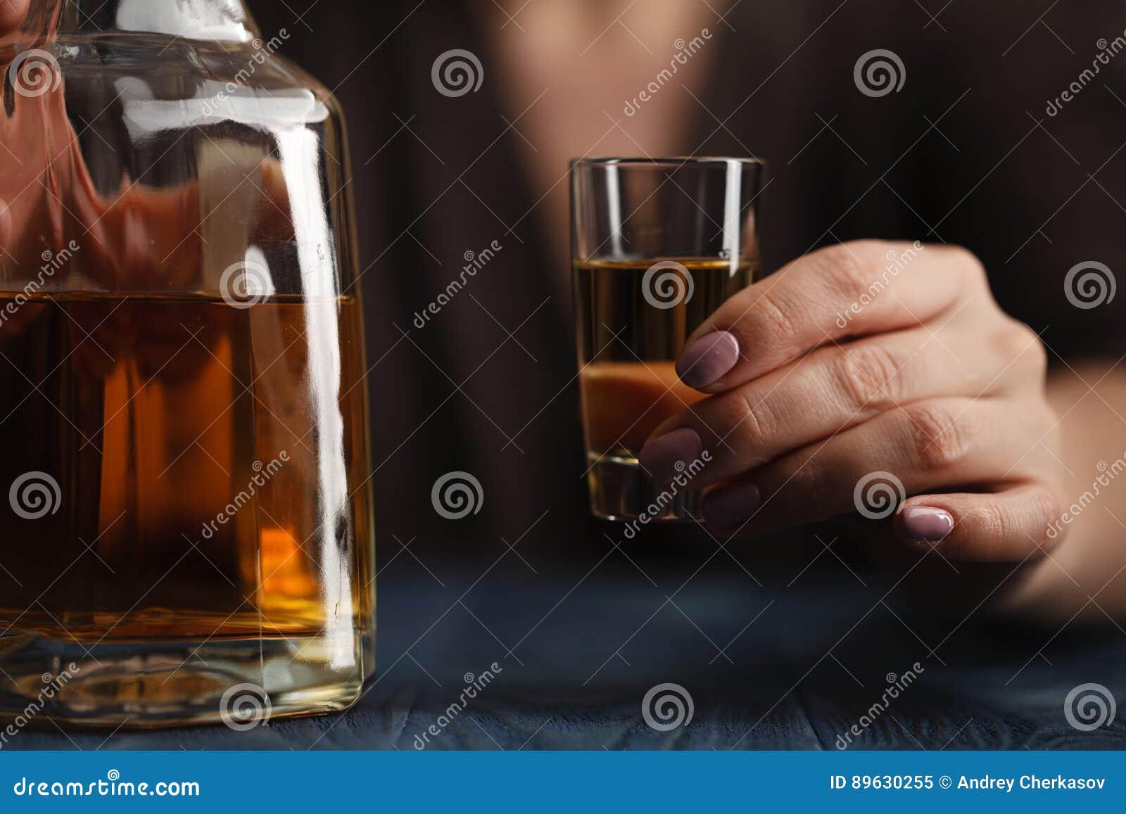 Alcohol de consumición de la mujer en fondo oscuro Foco en la copa de vino