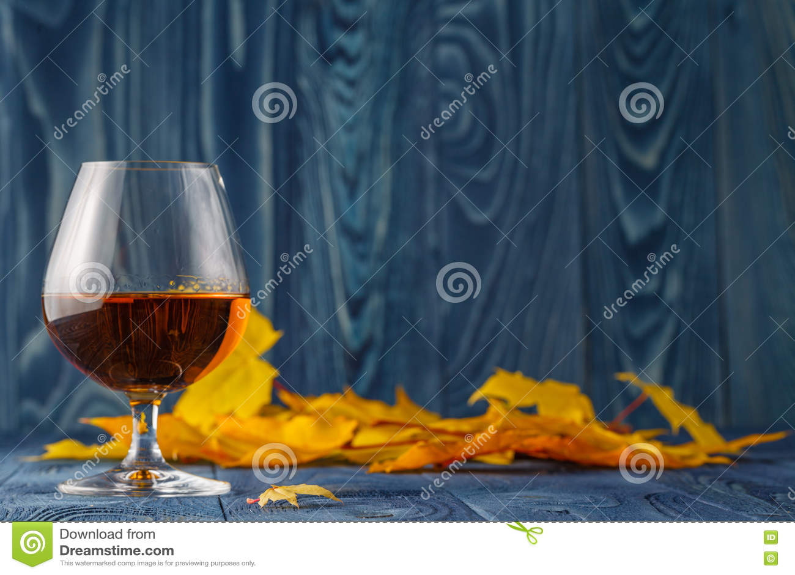 Alcohol estacional que bebe en la tabla azul con las hojas